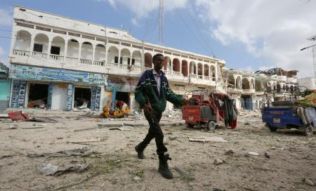 A Somali government soldier walks near the scene of an explosion in front of Dayah hotel in Somalia's capital Mogadishu, January 25, 2017.