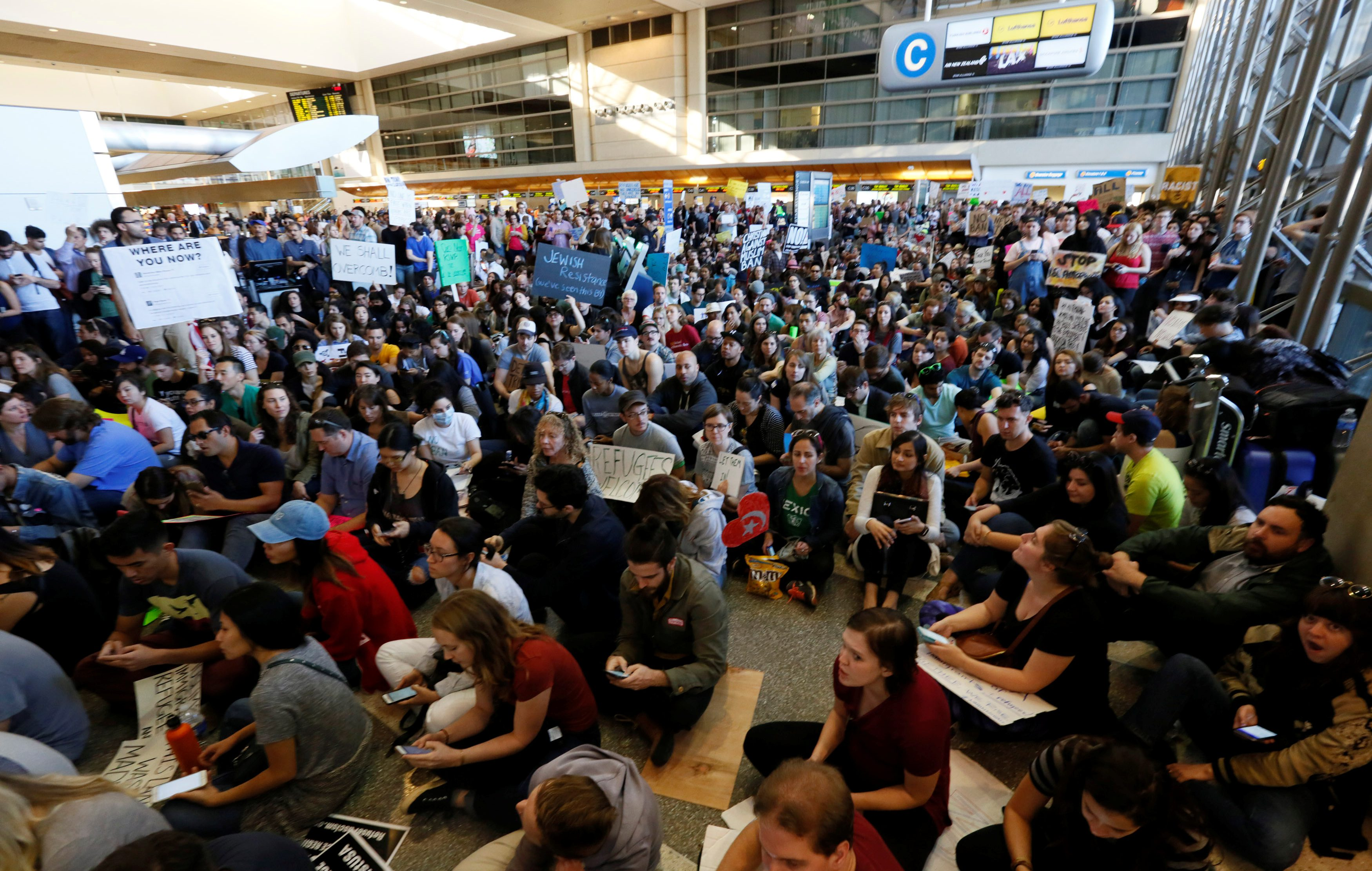 Demonstrators sit inside LAX international terminal and yell slogans during protest against the travel ban imposed by U.S. President Donald Trump's executive order, at Los Angeles International Airport in Los Angeles