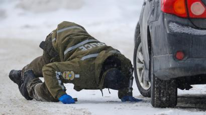 Police officer in Quebec City searches under a car