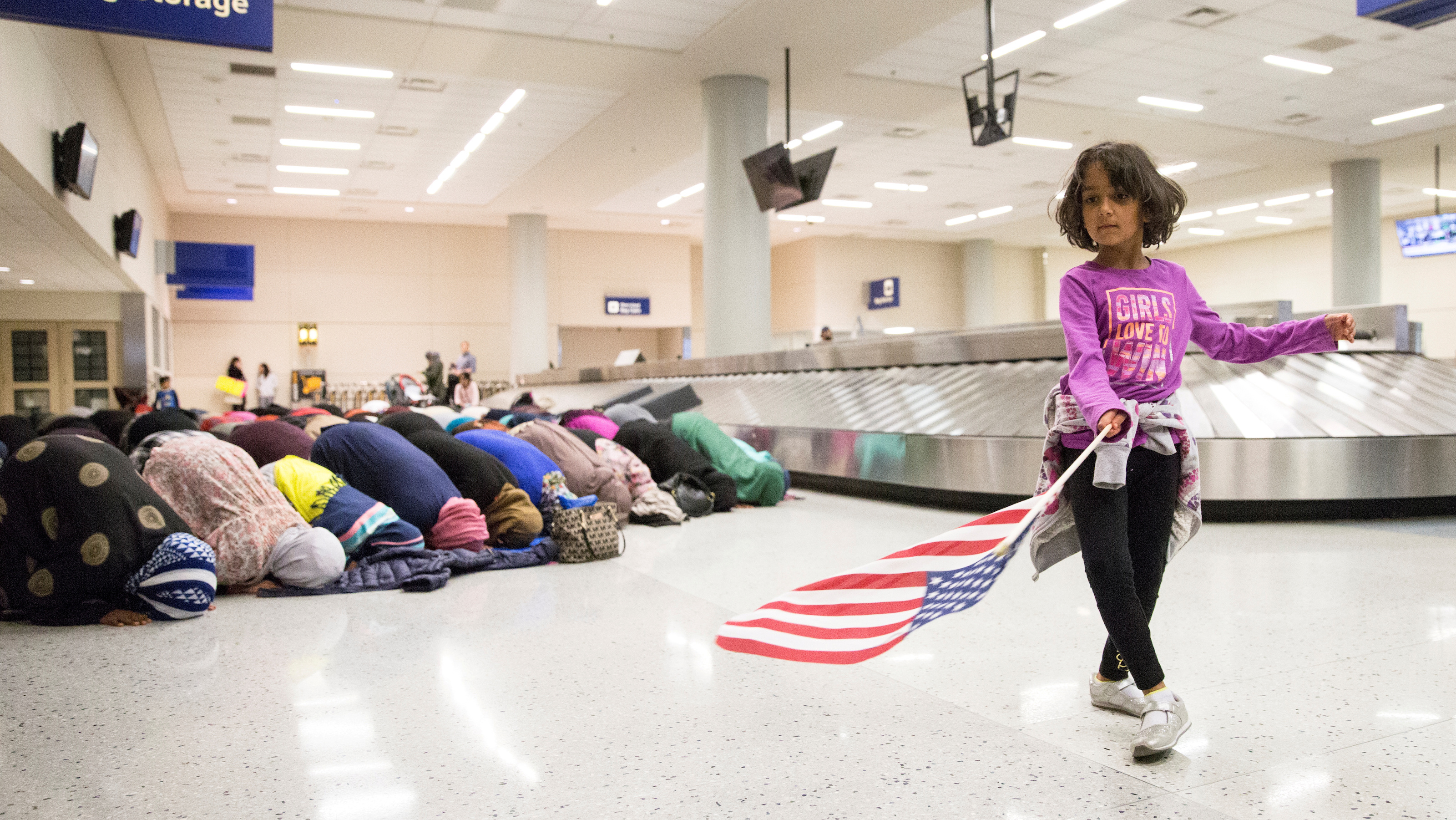 FILE PHOTO:A young girl dances with an American flag in baggage claim while women pray behind her during a protest against the travel ban imposed by U.S. President Donald Trump's executive order, at Dallas/Fort Worth International Airport in Dallas, Texas, U.S. January 29, 2017.  REUTERS/Laura Buckman/File Photo - RTSY3WY