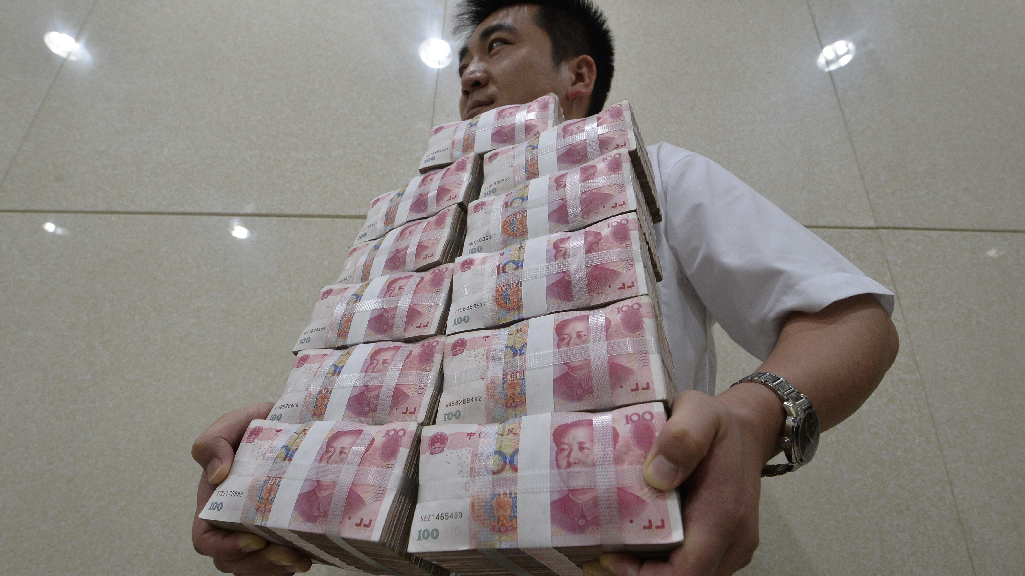 An employee carries bundles of 100 yuan Chinese bank notes to store after counting at a bank in Taiyuan, Shanxi province July 4, 2013. Chinese authorities allowed short-term borrowing costs to spike to record levels on June 20, sending a blunt but effective message to banks that it was determined to bring risky credit growth under control. The crackdown, however, has only increased China Inc's reliance on shadow banking and its various components, underscoring the system's importance as China's rigid financial industry maneuvers through an economic slowdown. Picture taken July 4, 2013.