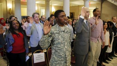 U.S. Army Private Asha Dalling (C) raises his hand as he takes the United States Oath of Citizenship during a naturalization ceremony in the Brooklyn borough of New York December 15, 2015. REUTERS/Lucas Jackson - RTX1YV1U