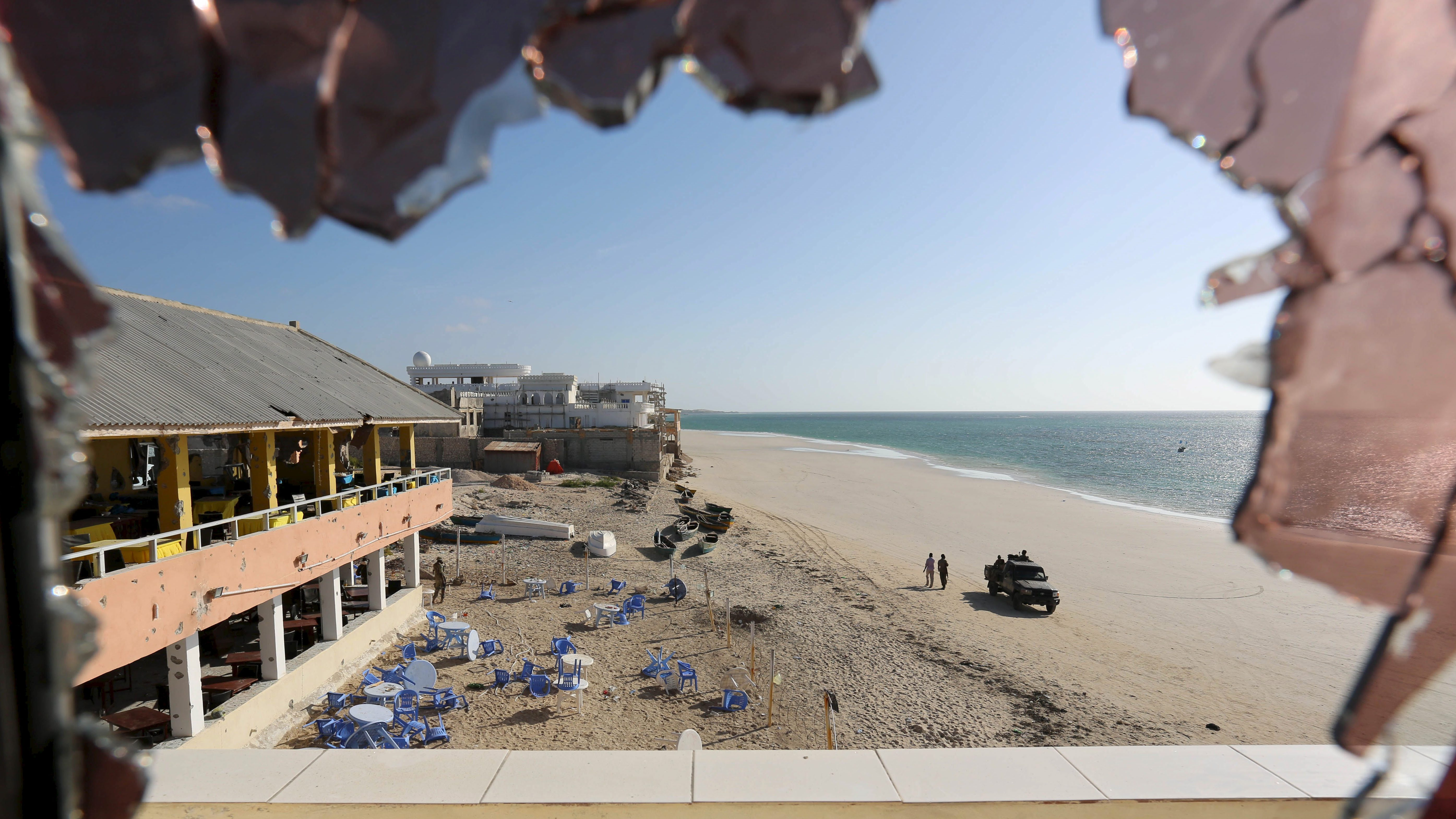 A general view through a broken glass shows government forces patrolling on Lido beach following an attack at beachside restaurant Beach View Cafe in Somalia's capital Mogadishu, January 22, 2016.
