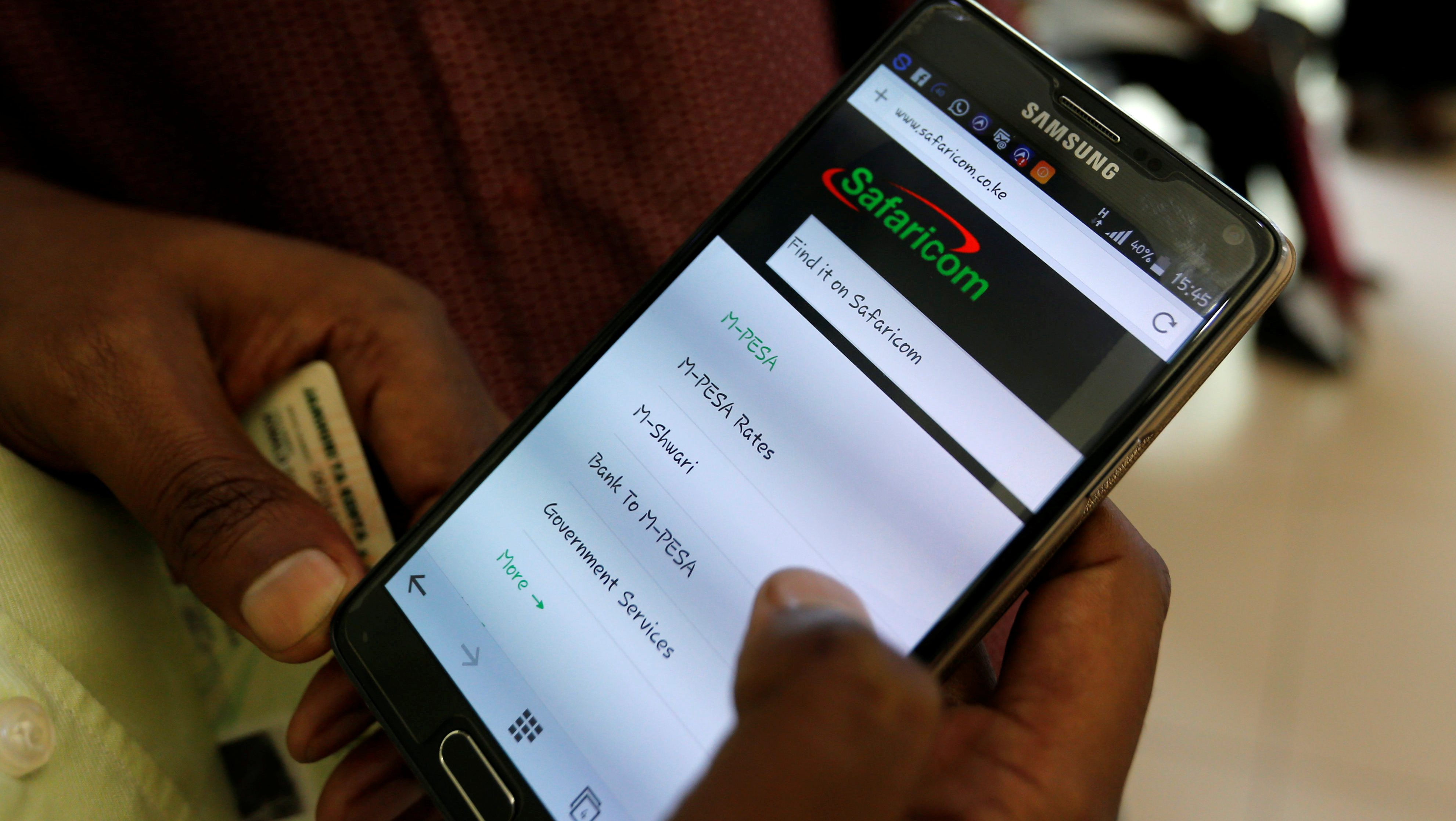 An employee assists a customer to set-up M-Pesa money transfer servive on his handset inside a mobile phone care centre operated by Kenyan's telecom operator Safaricom; in the central business district of Kenya's capital Nairobi, May 11, 2016. REUTERS/Thomas Mukoya - RTX2DU5V