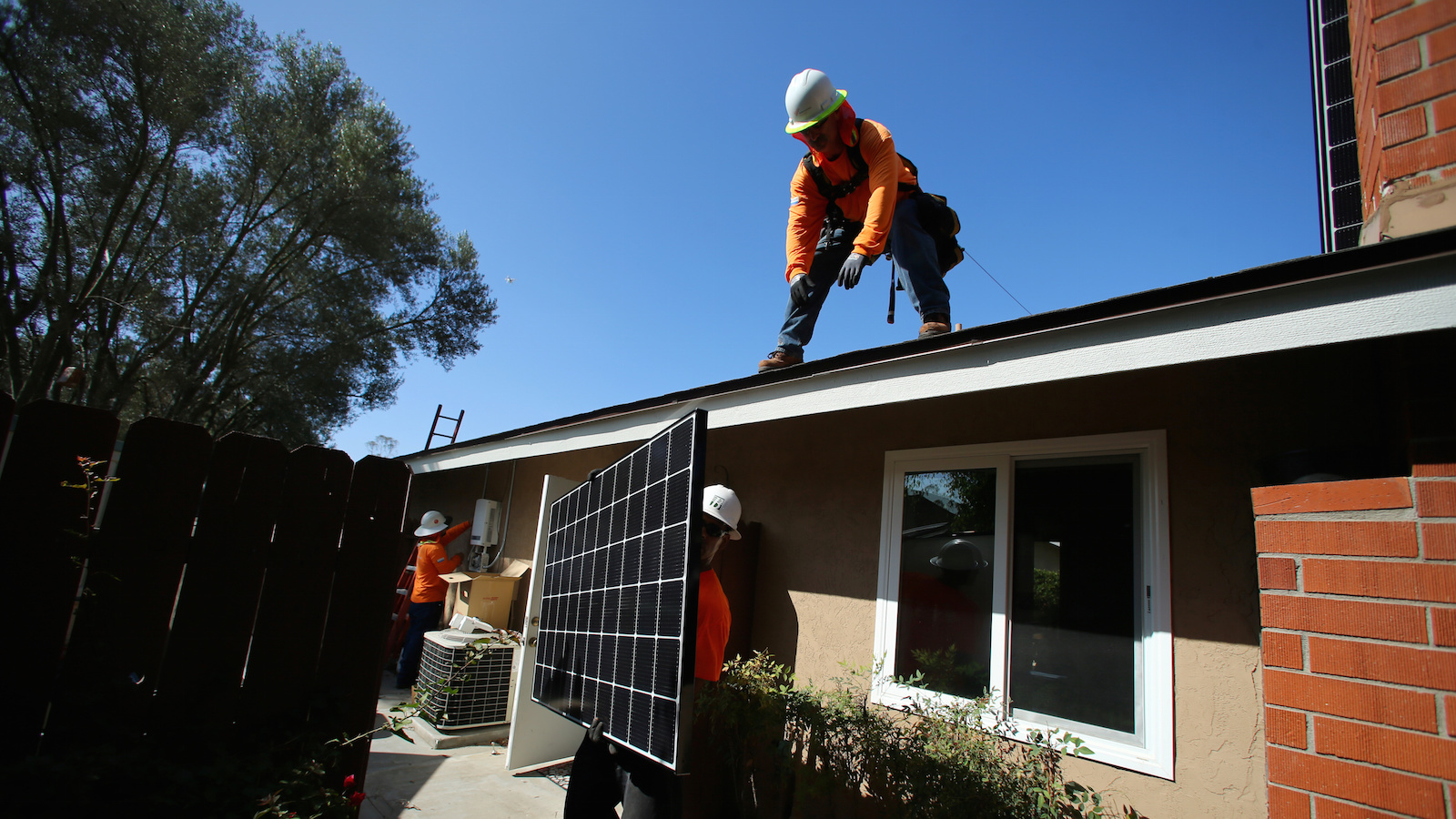 Workers lift a solar panel onto a roof during a residential solar installation in Scripps Ranch, San Diego, California, U.S. October 14, 2016. Picture taken October 14, 2016.       REUTERS/Mike Blake - RTX2QGX8