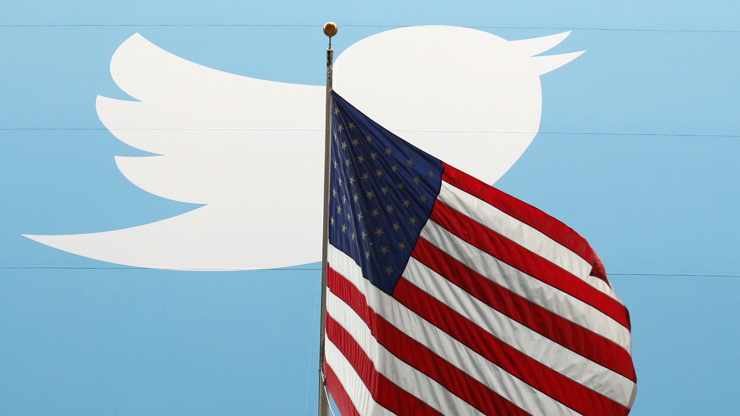 The Twitter Inc. logo is shown with the U.S. flag during the company's IPO on the floor of the New York Stock Exchange in New York, November 7, 2013.    REUTERS/Lucas Jackson/File Photo - RTX2V9CB