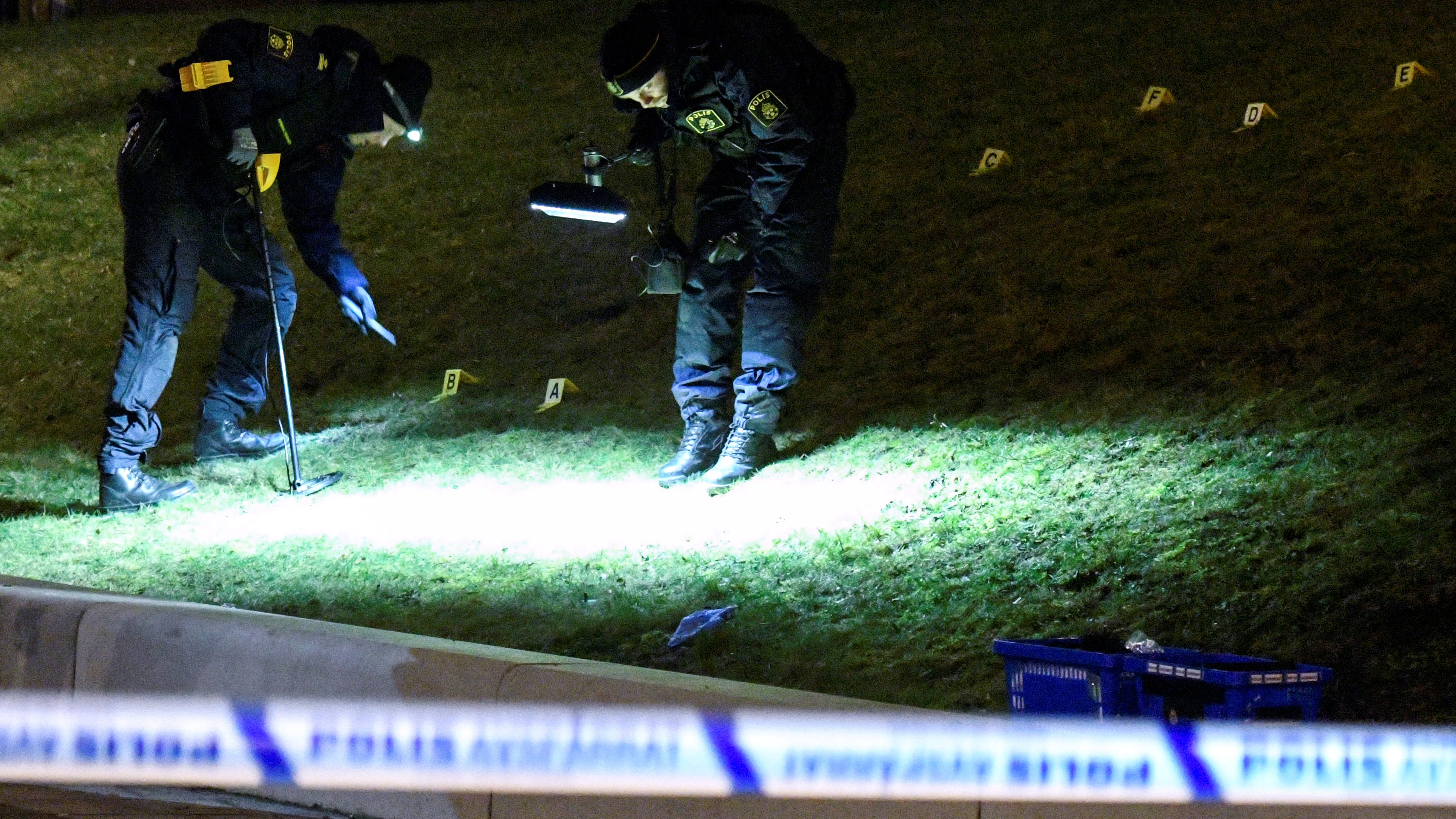 Police crime scene investigators work next to a bus stop in the Rosengard district in Malmo