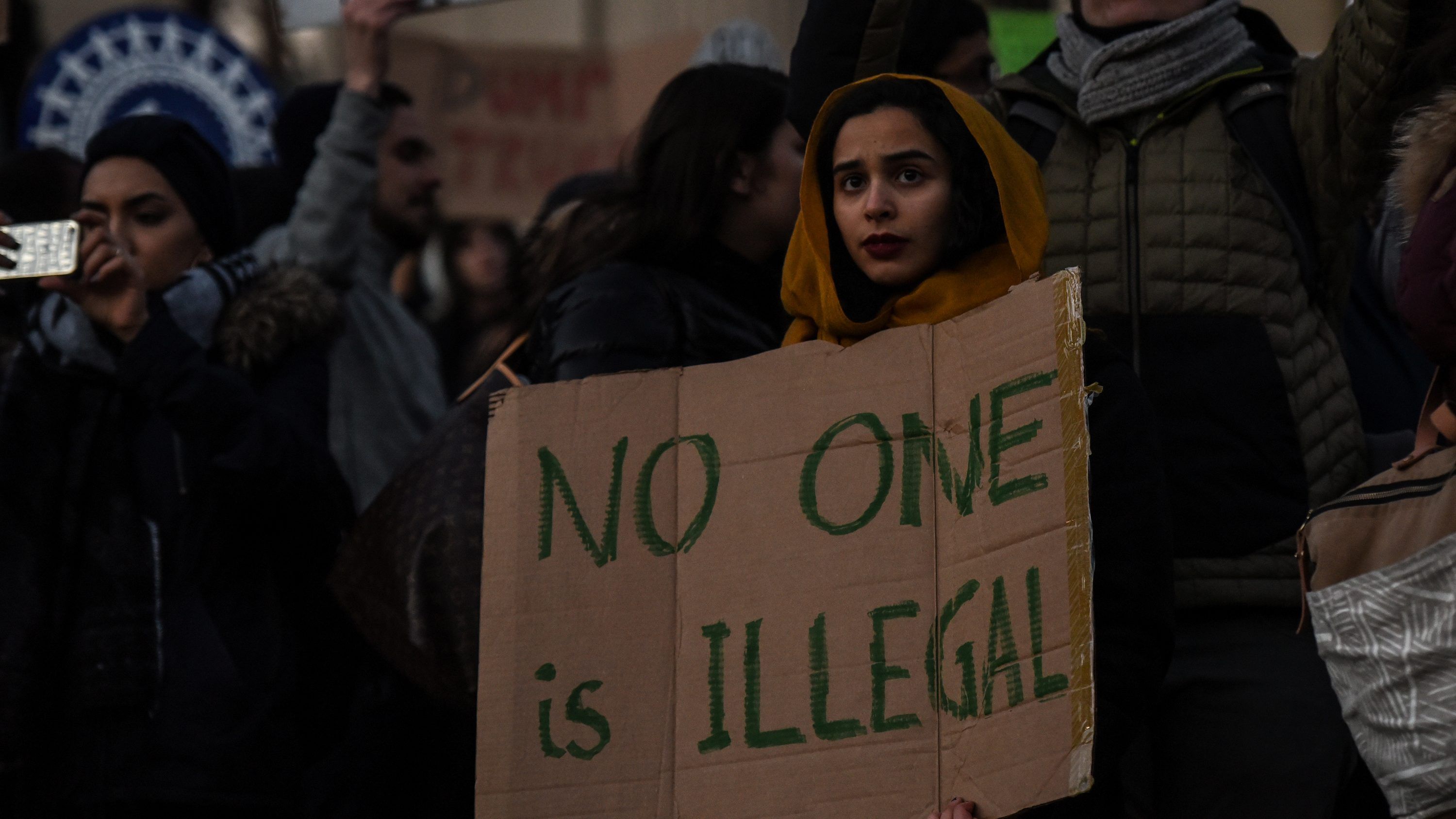 People participate in a protest against President Donald Trump's muslim ban.