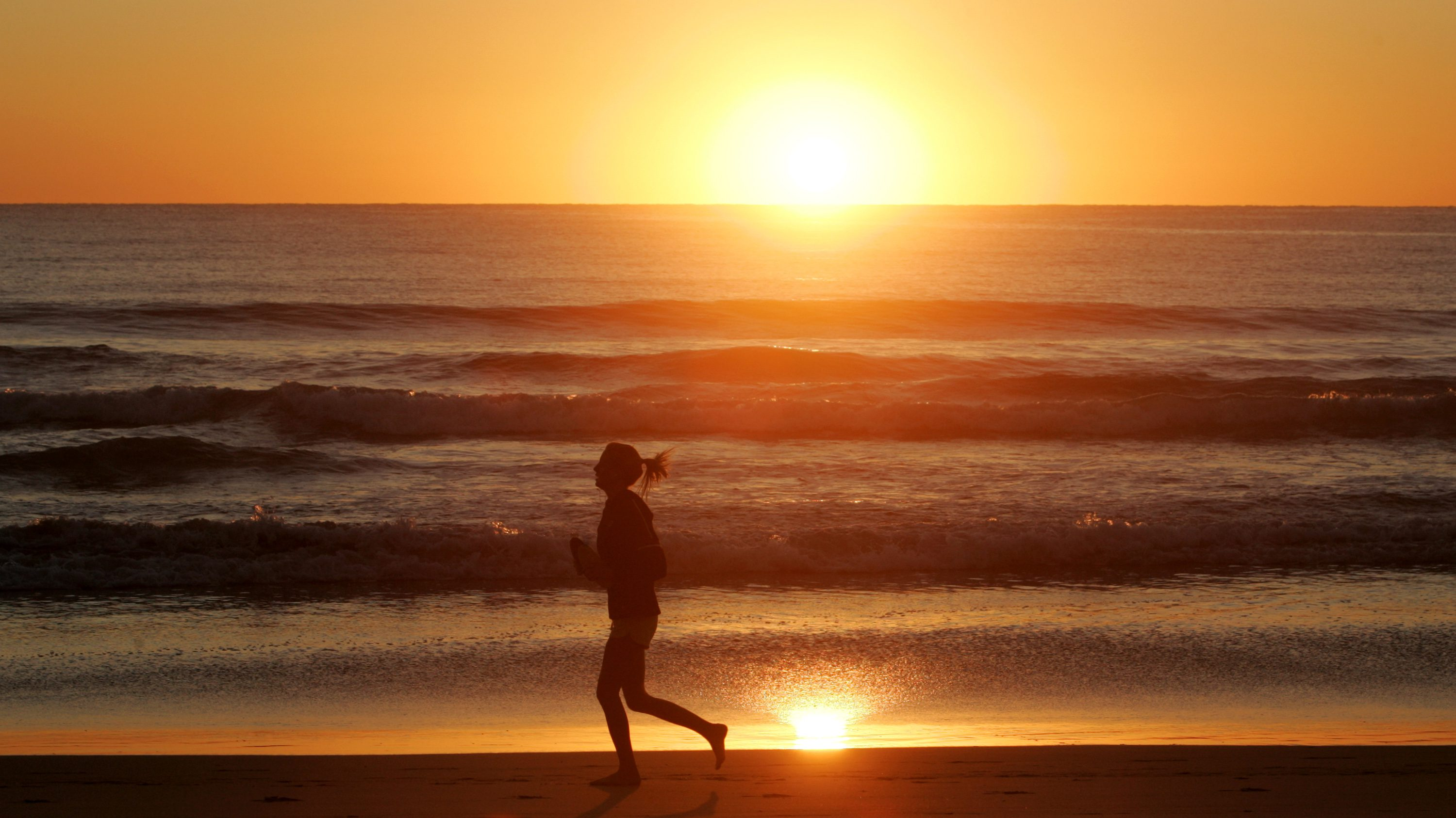 A jogger runs along the shore of Manly Beach after sunrise on the first day of Spring in Sydney September 1, 2008.