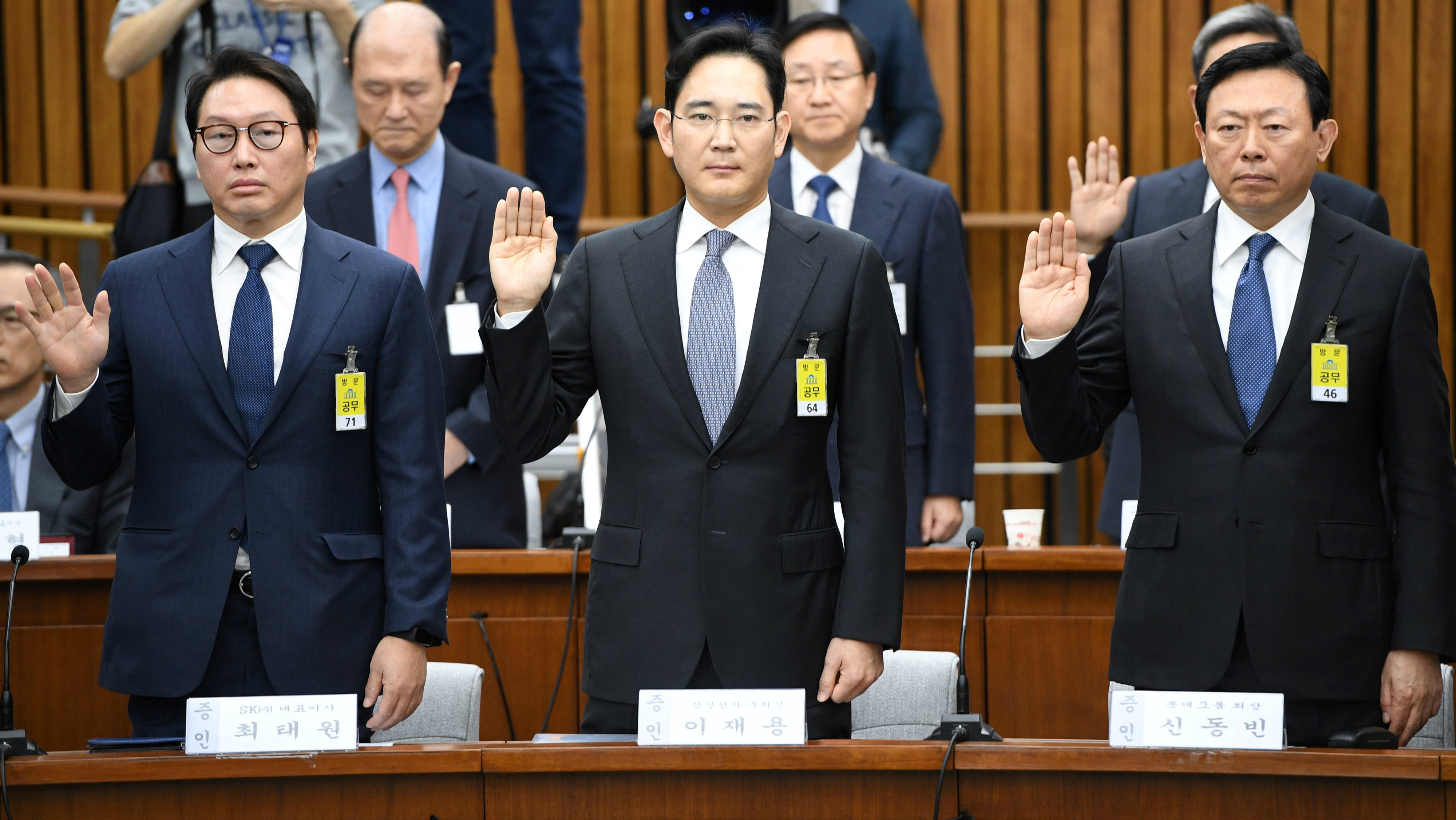 SK Group chairman Chey Tae-Won, Samsung Group's heir-apparent Lee Jae-yong and Lotte Group Chairman Shin Dong-Bin take an oath during a parliamentary probe into a scandal engulfing President Park Geun-Hye at the National Assembly in Seoul on December 6, 2016.