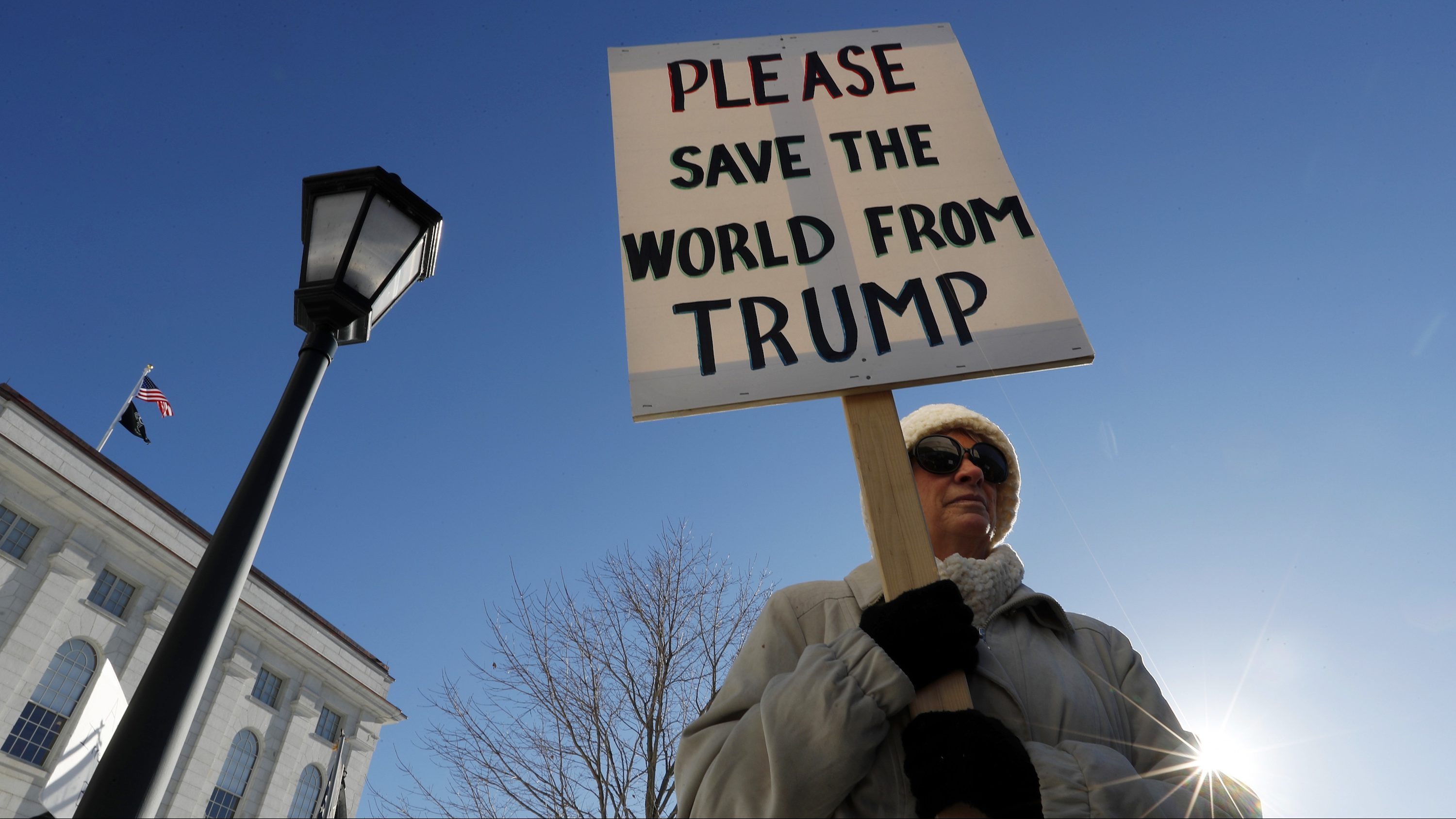 Davina Foti, of Exeter, N.H., attends a protest against President-elect Donald Trump Monday, Dec. 19, 2016, at the State House in Augusta, Maine. Maine's electoral college voters split their vote with 3 ballots for Hillary Clinton and one for Trump.