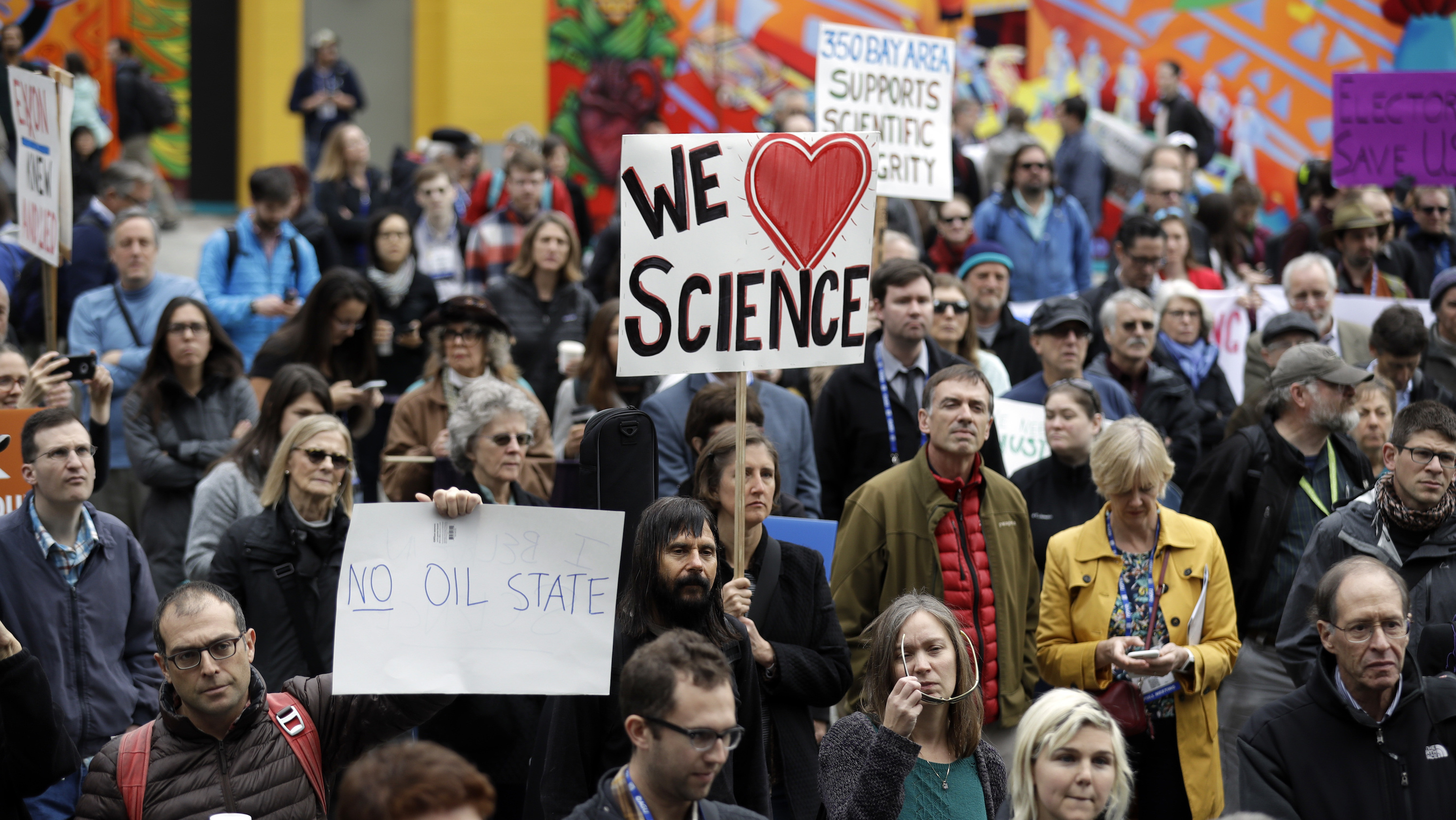 People hold signs as they listen to a group of scientists speak during a rally in conjunction with the American Geophysical Union's fall meeting Tuesday, Dec. 13, 2016, in San Francisco. The rally was to call attention to what scientist believe is unwarranted attacks by the incoming Trump administration against scientists advocating for the issue of climate change and its impact.