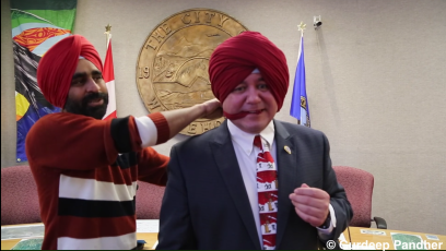 Dan Curtis, the mayor of the Canadian city Whitehorse, in the process of putting on a Sikh turban.