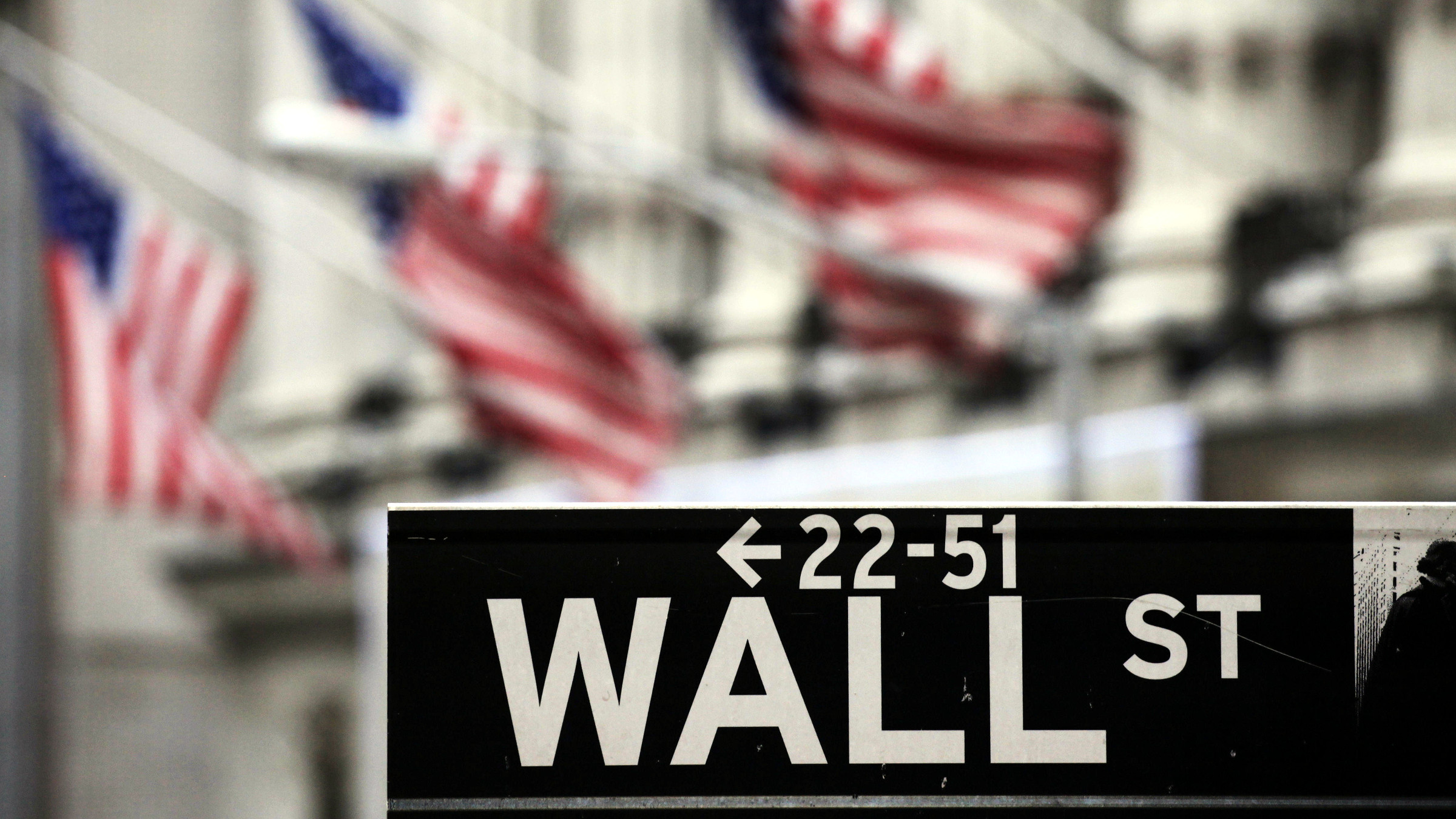 A Wall Street sign is shown in front of the New York Stock Exchange, Thursday, April 22, 2010. President Barack Obama gives a speech later in the day in New York regarding regulation of the financial community.