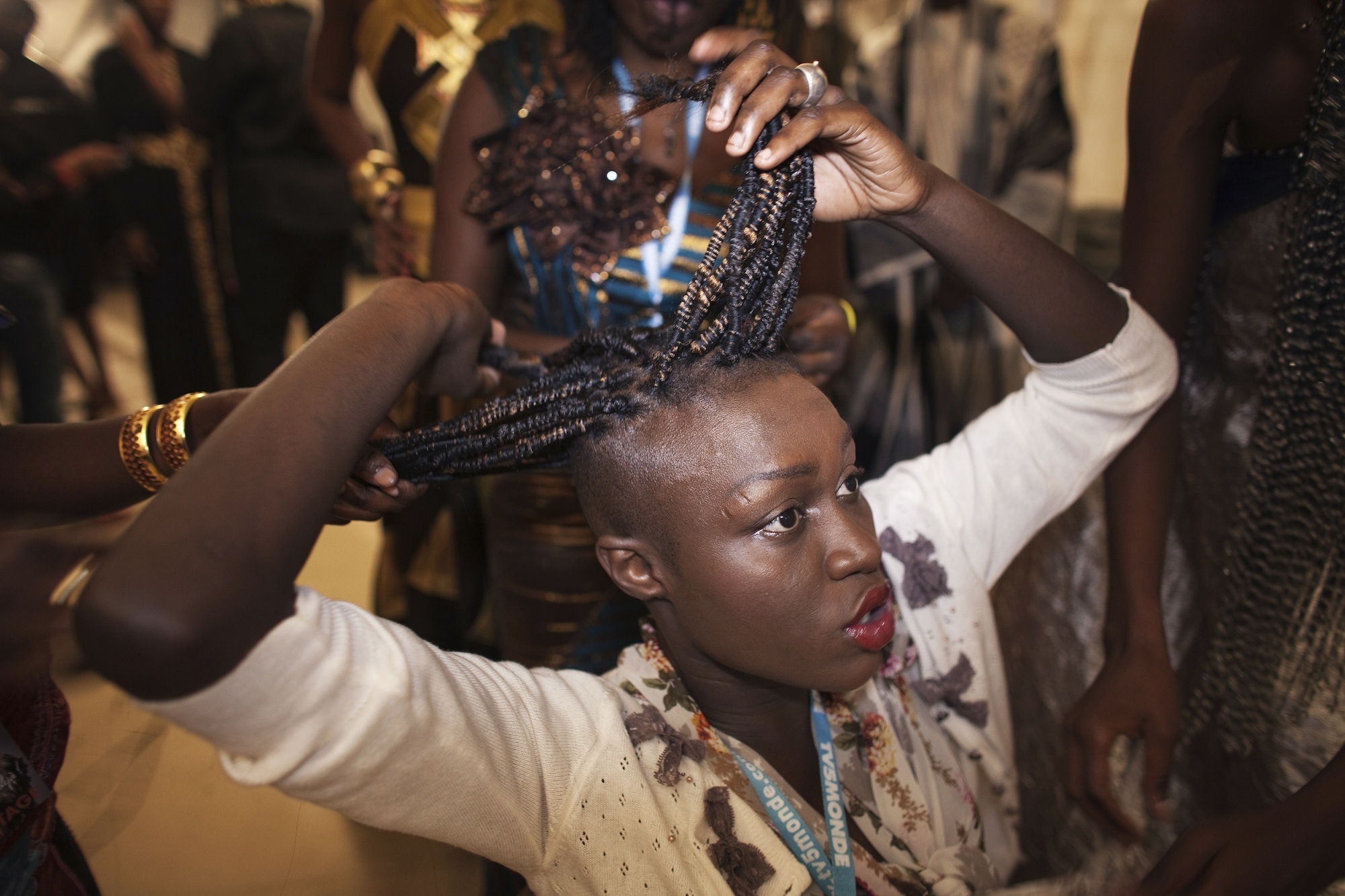 Senegalese model Sachakara Dieng has her hair done backstage during the 10th anniversary of Dakar Fashion Week June 15, 2012.