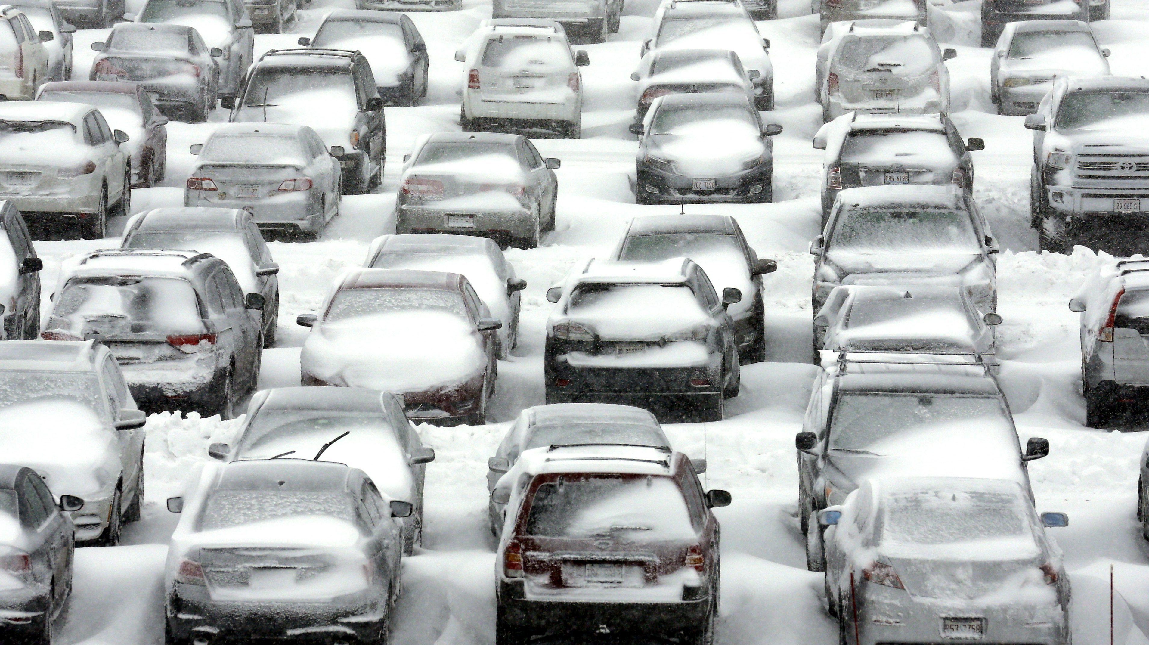 Cars covered with snow in a parking lot.