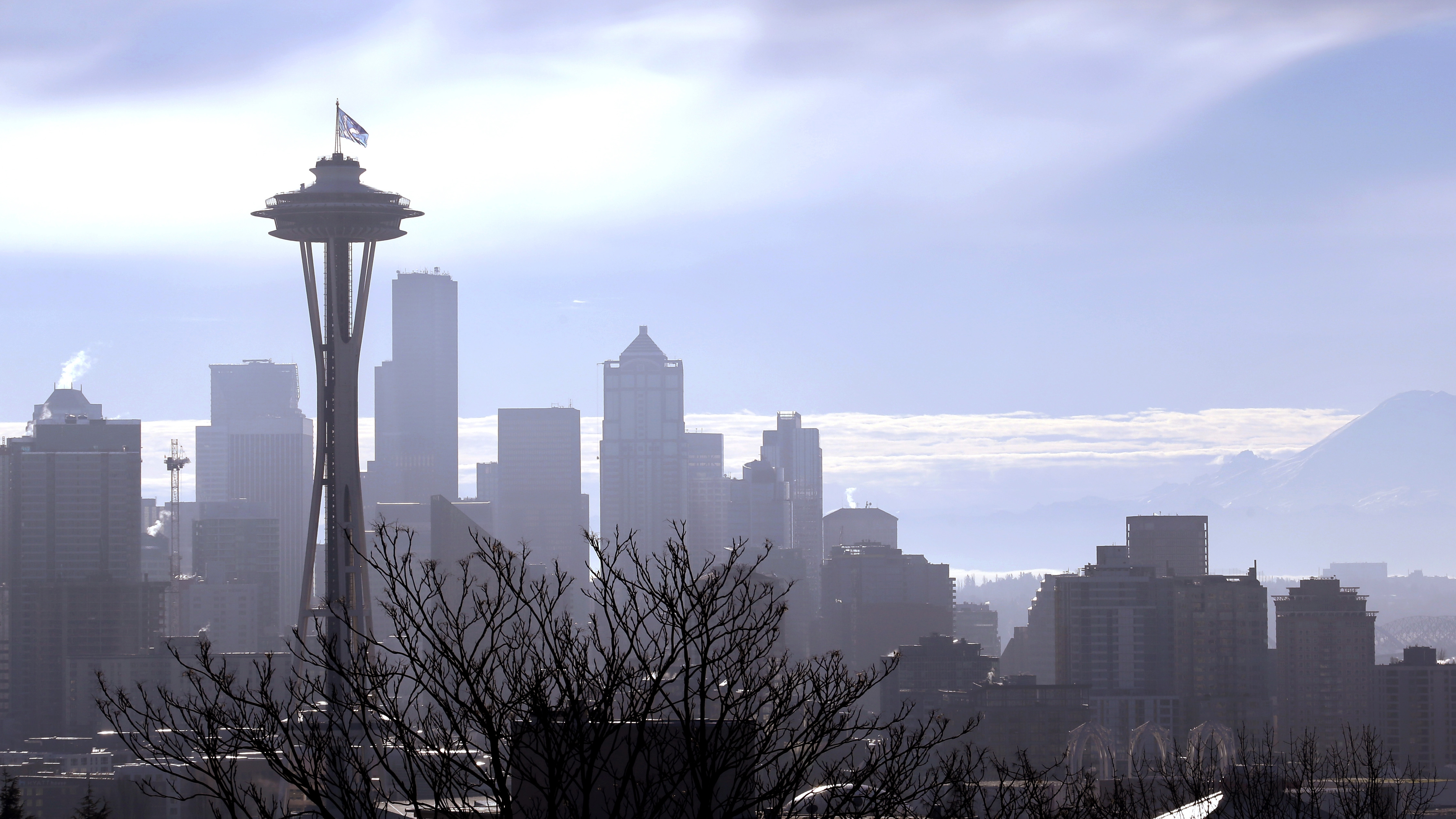 "With Mount Rainier, right, visible in the distance, a ""12th Man"" flag, honoring Seattle Seahawks fans, flutters atop the Space Needle after being raised Thursday morning, Jan. 29, 2015, in Seattle. The 25 foot by 35 foot flag will fly atop the 605 foot tall structure through Sunday's Super Bowl XLIX NFL football game between the Seahawks and New England Patriots. (AP Photo/Elaine Thompson)"