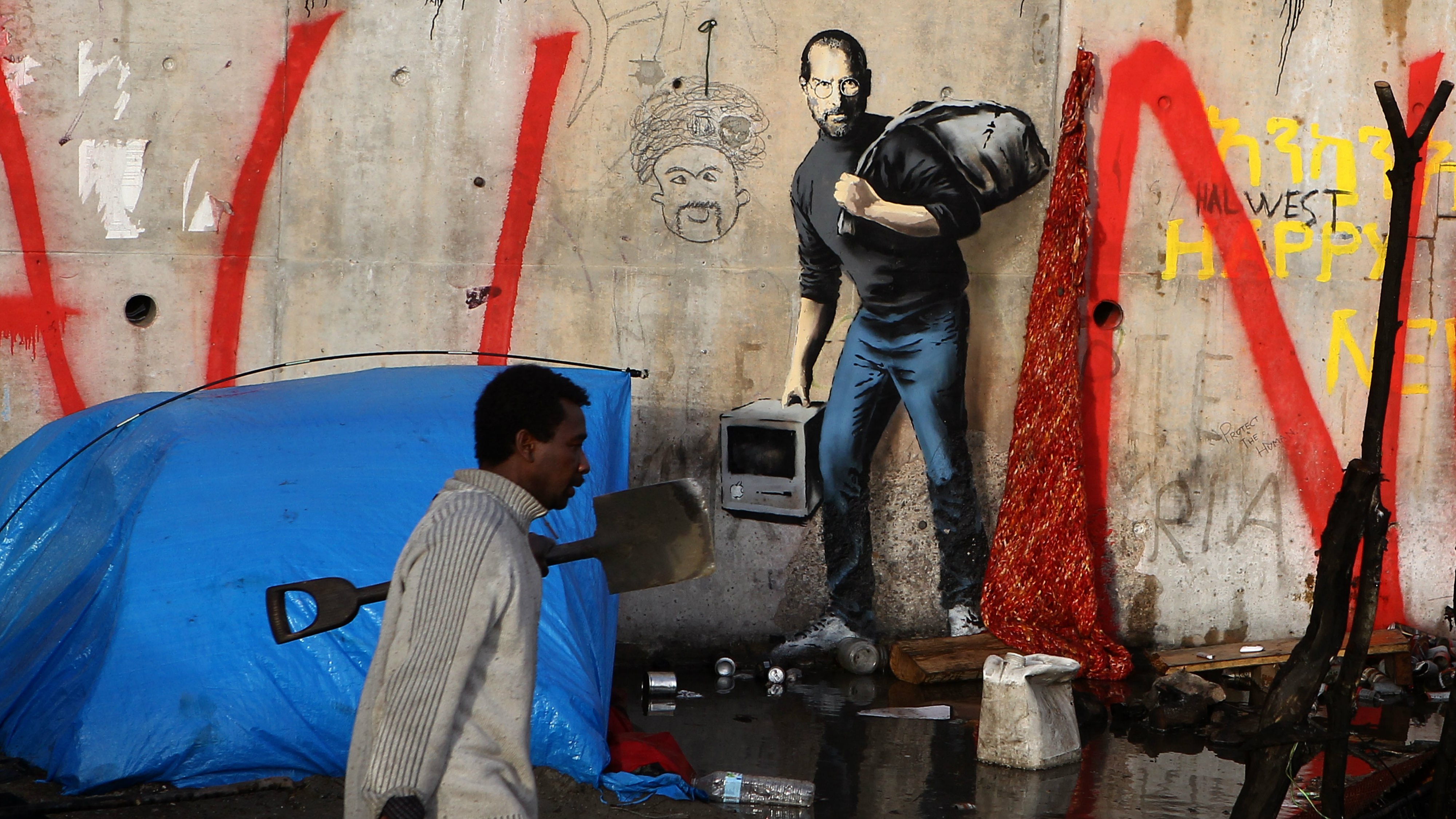 A migrant walks past a painting by English graffiti artist Banksy, at the entrance of the Calais refugee camp in France, in Calais, northern France, Monday, Dec. 21, 2015. The elusive graffiti artist has depicted the late Apple guru Steve Jobs — whose biological father was from Syria — carrying a black garbage bag and an early model of the Macintosh computer.