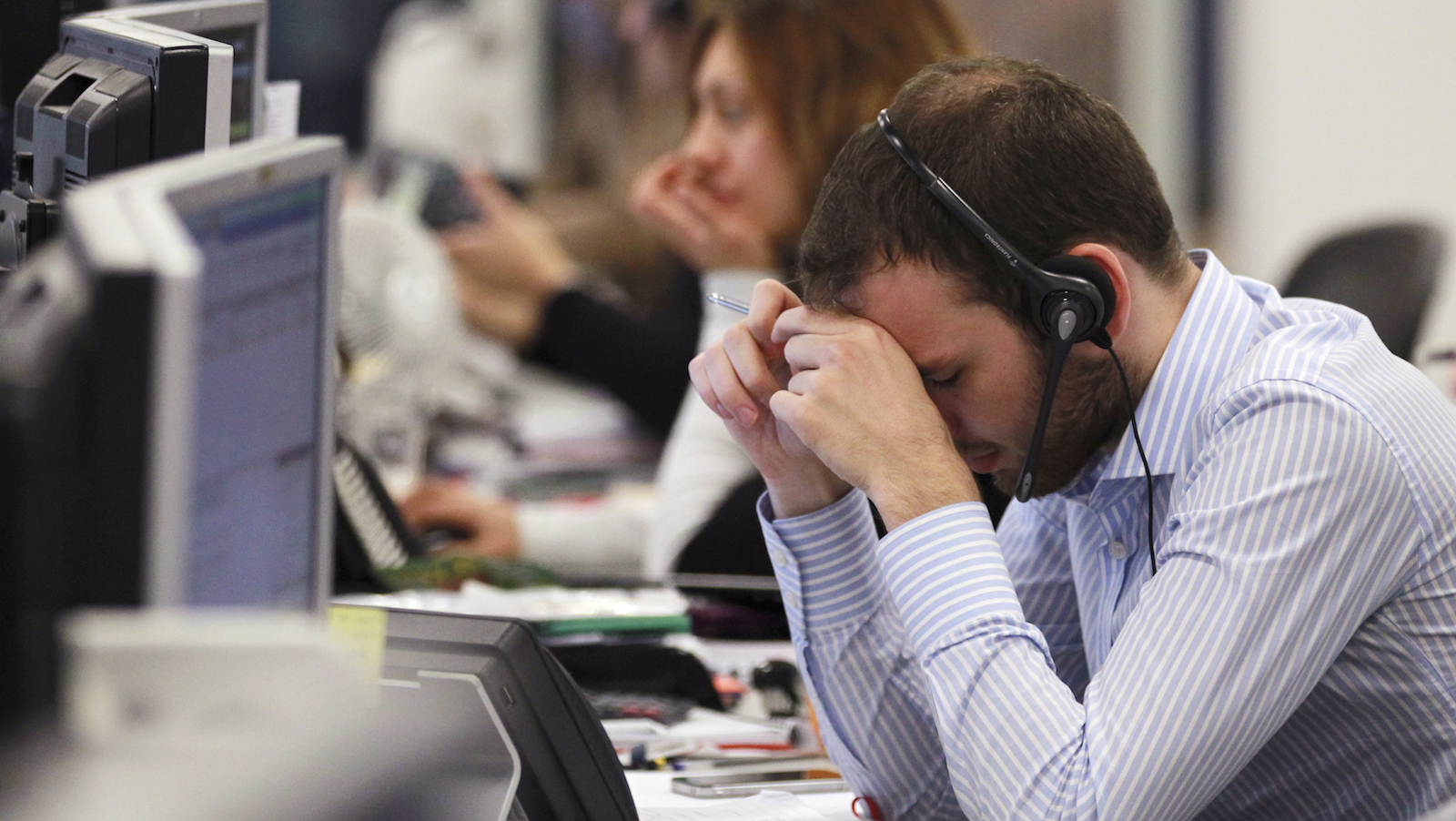 A worker on the IG Group's trading floor looks away from his screens in the City of London, October 4, 2011. Britain's top share index fell sharply by midday on Tuesday as worries over the euro zone debt crisis and the sustainability of global growth prompted investors to cut positions in riskier assets such as banks and commodity stocks.
