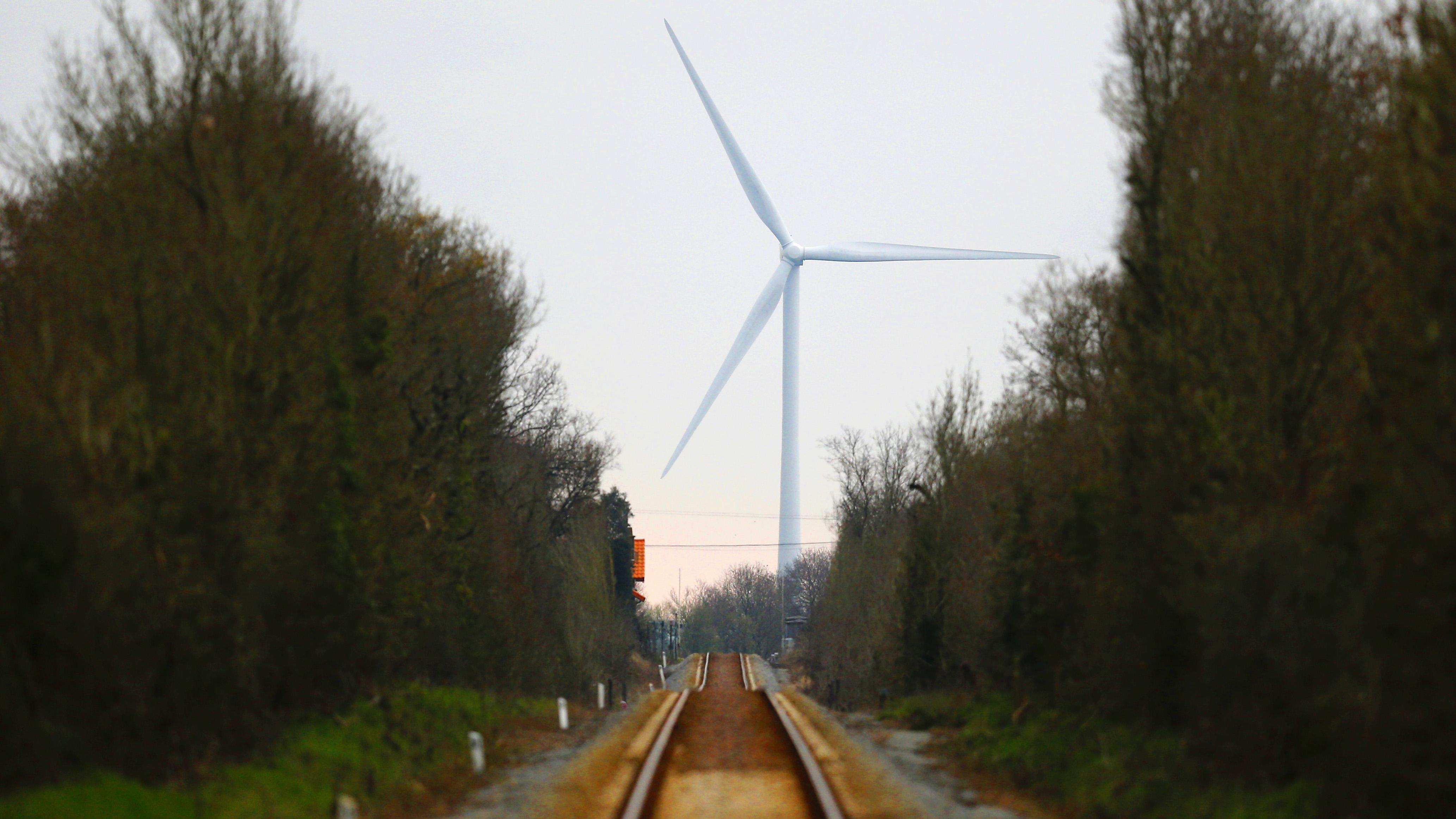 A wind turbine is seen near railway tracks field in Bourgneuf-en-Retz, France, March 10, 2016. REUTERS/Stephane Mahe  - RTSA8JM