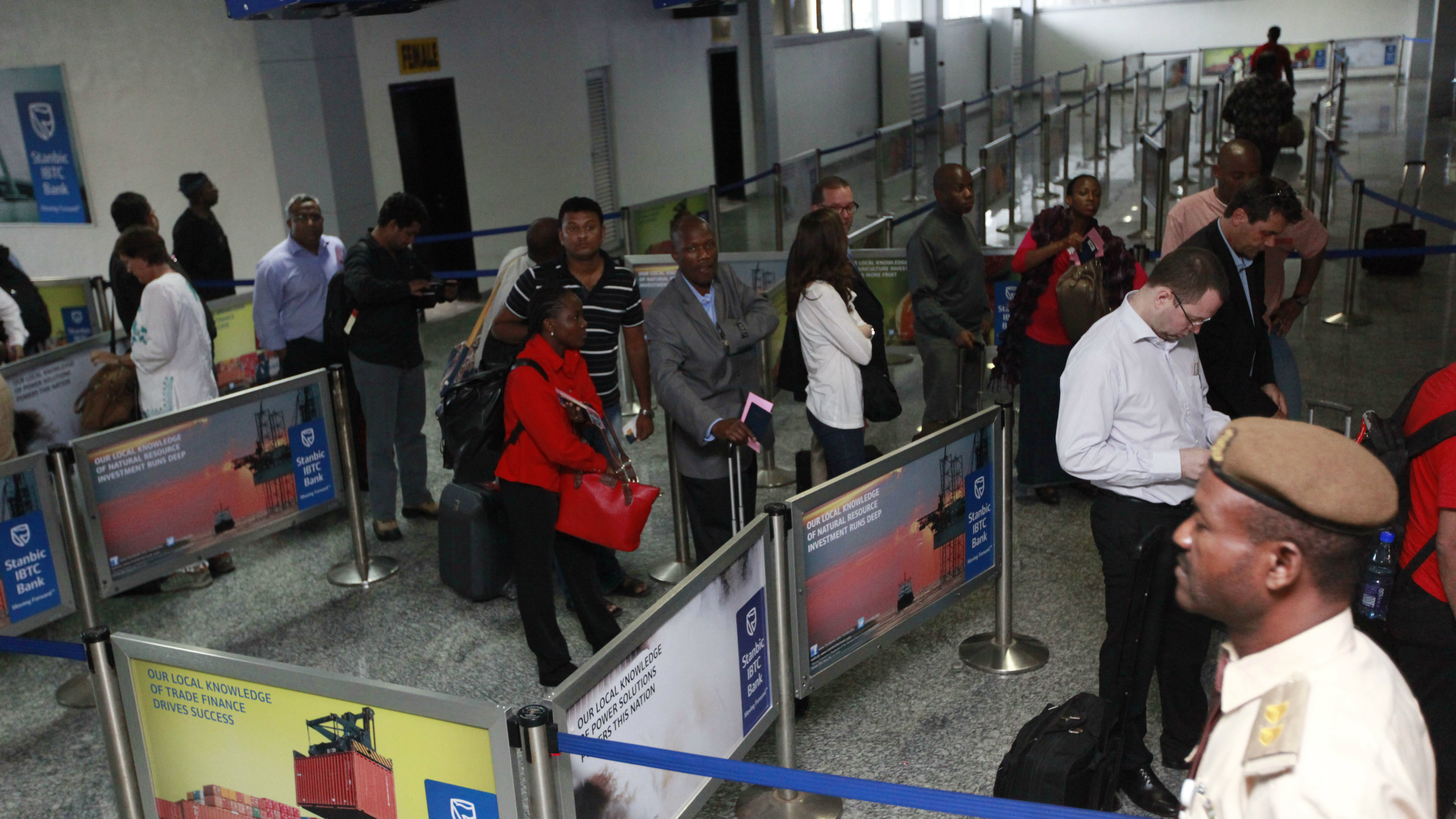 Passengers queue for their passport document check by immigration officers at the arrivals hall of Murtala Muhammed International Airport in Lagos, Nigeria, Monday, Aug. 4, 2014.
