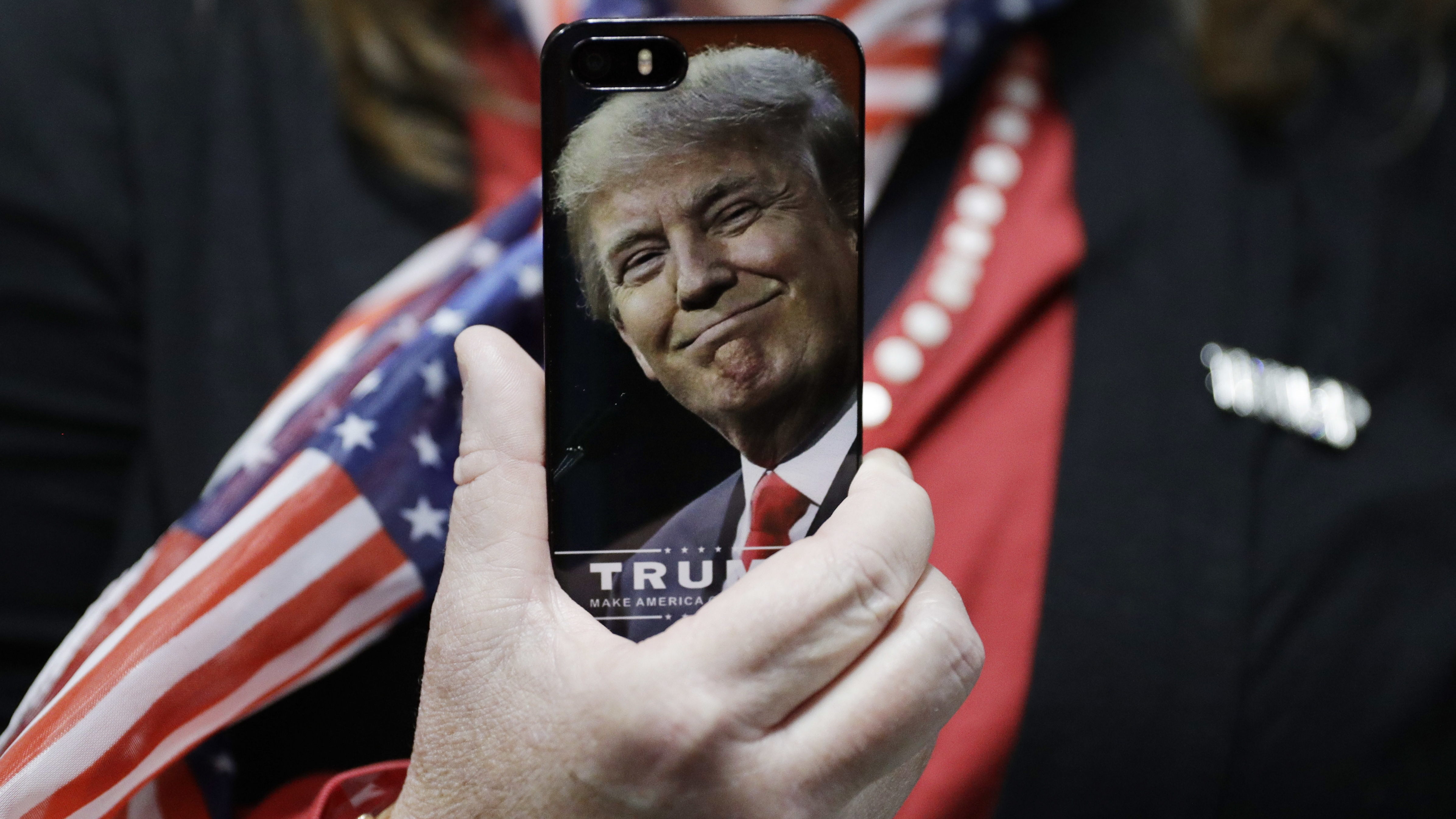 A woman holds up her cell phone before a rally with Republican presidential candidate Donald Trump, Thursday, Sept. 29, 2016, in Bedford, N.H. (AP Photo/John Locher)