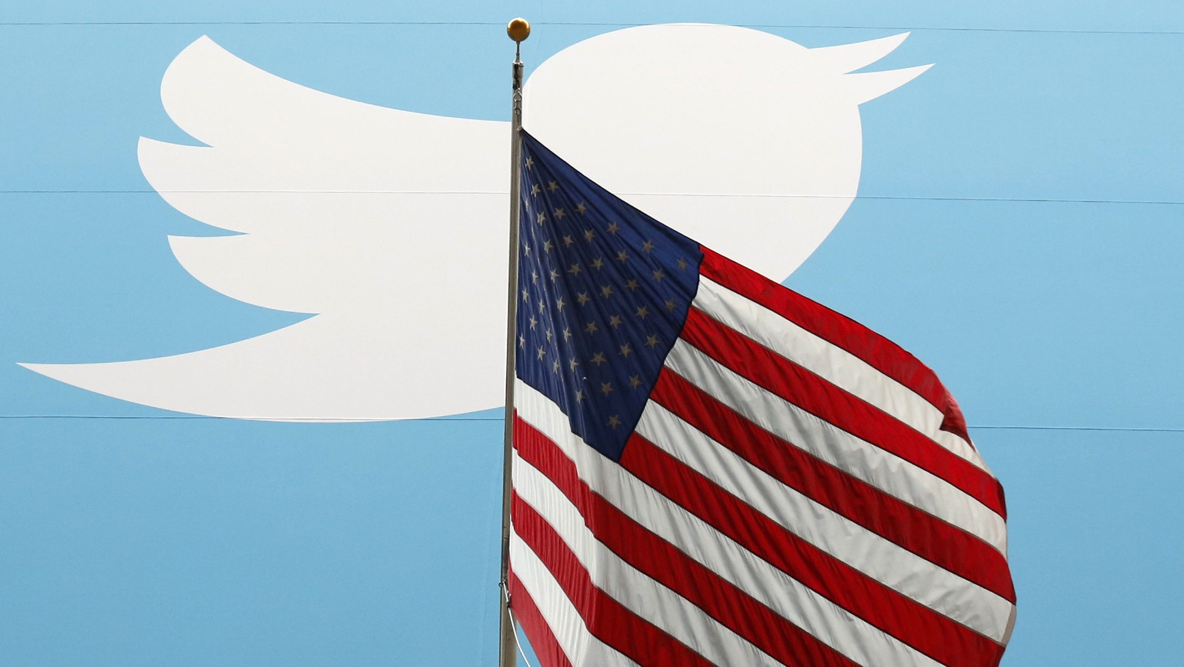 The Twitter Inc. logo is shown with the U.S. flag during the company's IPO on the floor of the New York Stock Exchange in New York, November 7, 2013.