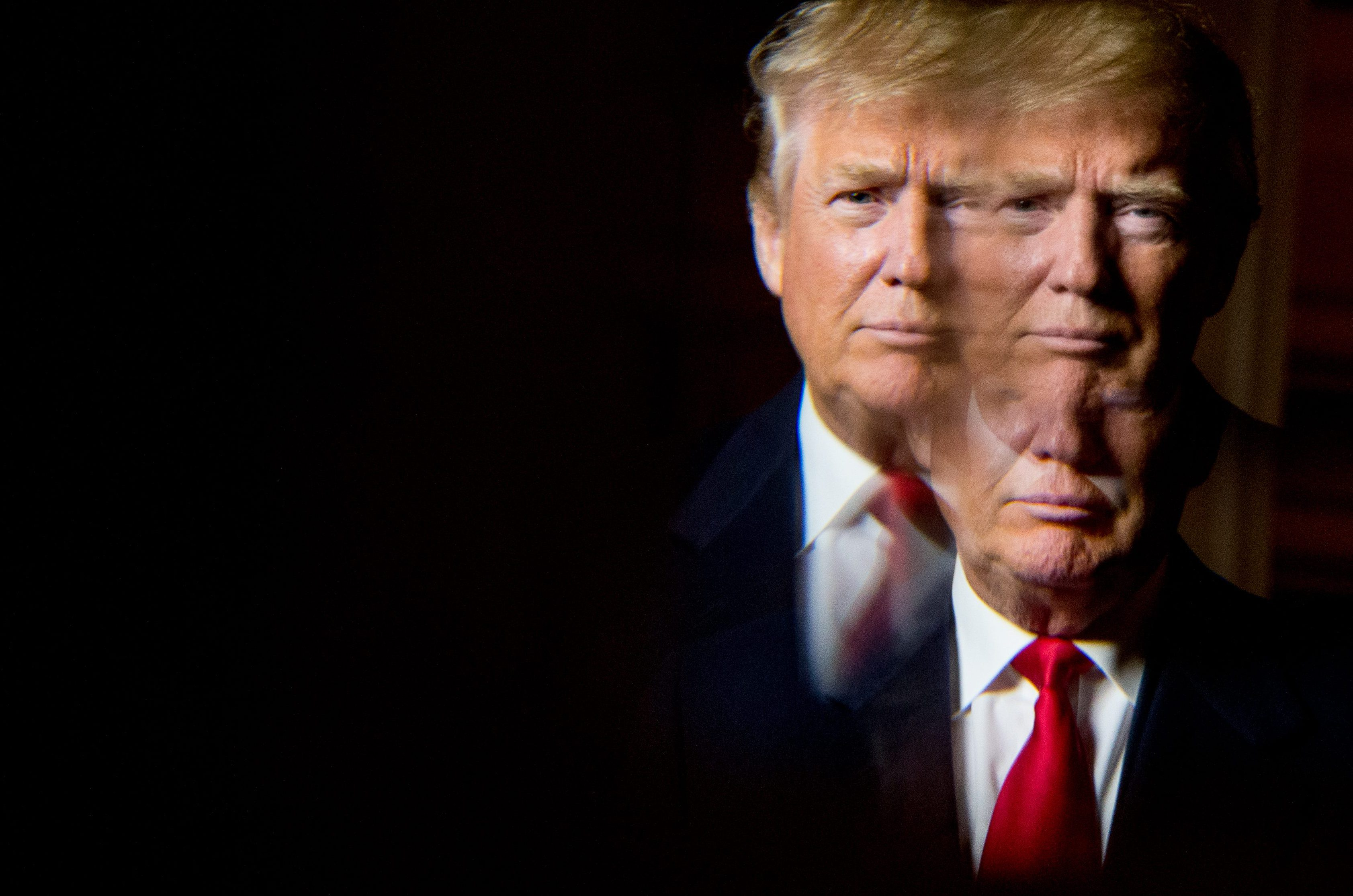 Republican presidential candidate Donald Trump, seen in reflection, poses for a portrait following an interview with the Associated Press at the Trump National Golf Club in Sterling, Va., Wednesday, Dec. 2, 2015. Trump says that if he's elected president, he'll know within six months whether he can achieve an elusive peace accord between Israelis and Palestinians, one of the world's most vexing challenges. But the Republican presidential candidate says he has doubts about each side's commitment to the peace process.