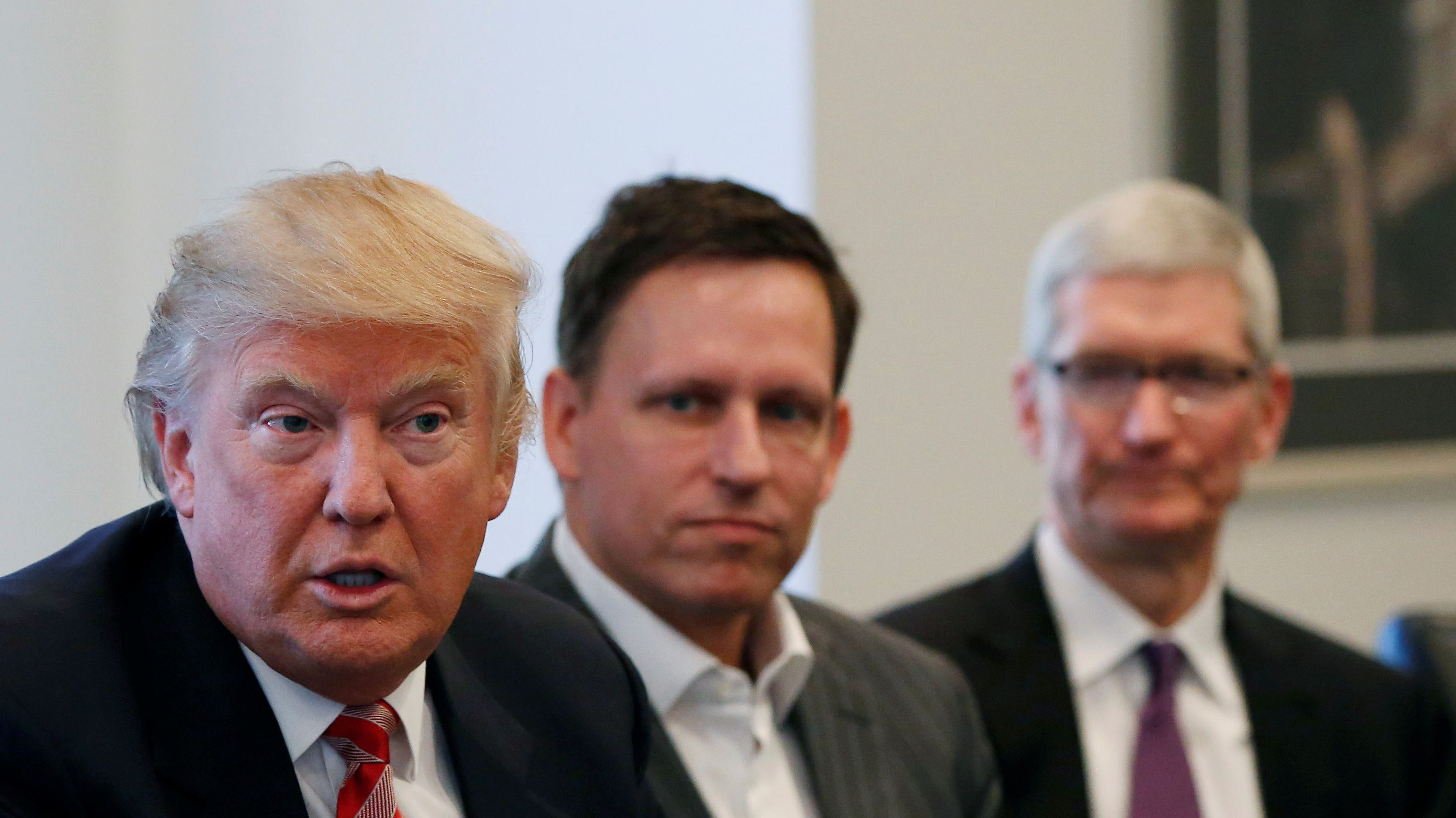 Apple CEO Tim Cook listens as President-elect Donald Trump speaks during a meeting with technology industry leaders at Trump Tower in New York, Wednesday, Dec. 14, 2016.