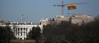 Greenpeace activists hold an anti-Trump protest as they display a banner reading 'Resist' from a construction crane near the White House in downtown Washington