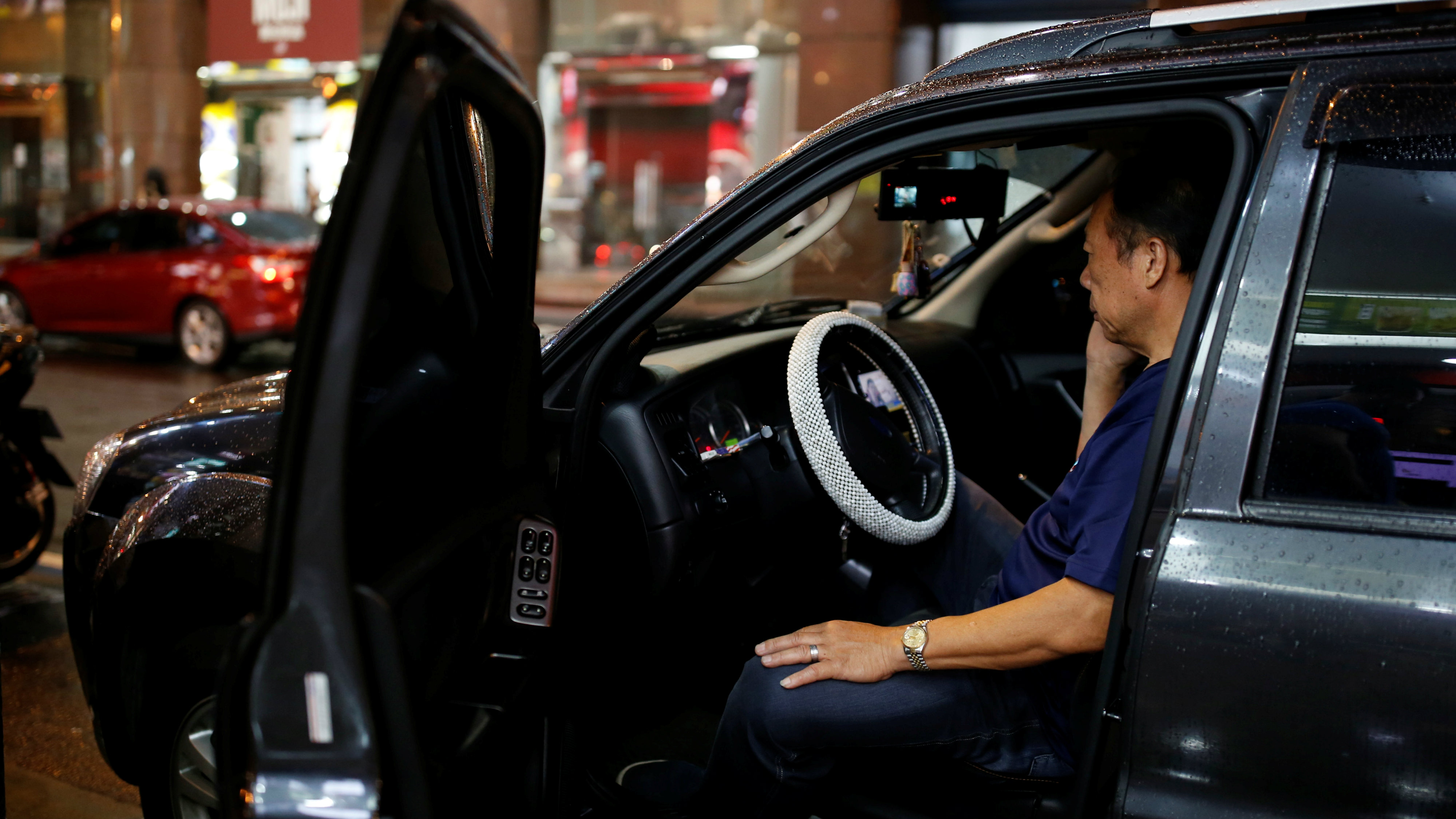 A man uses his mobile phone as he sits in a luxury car in Taipei, Taiwan