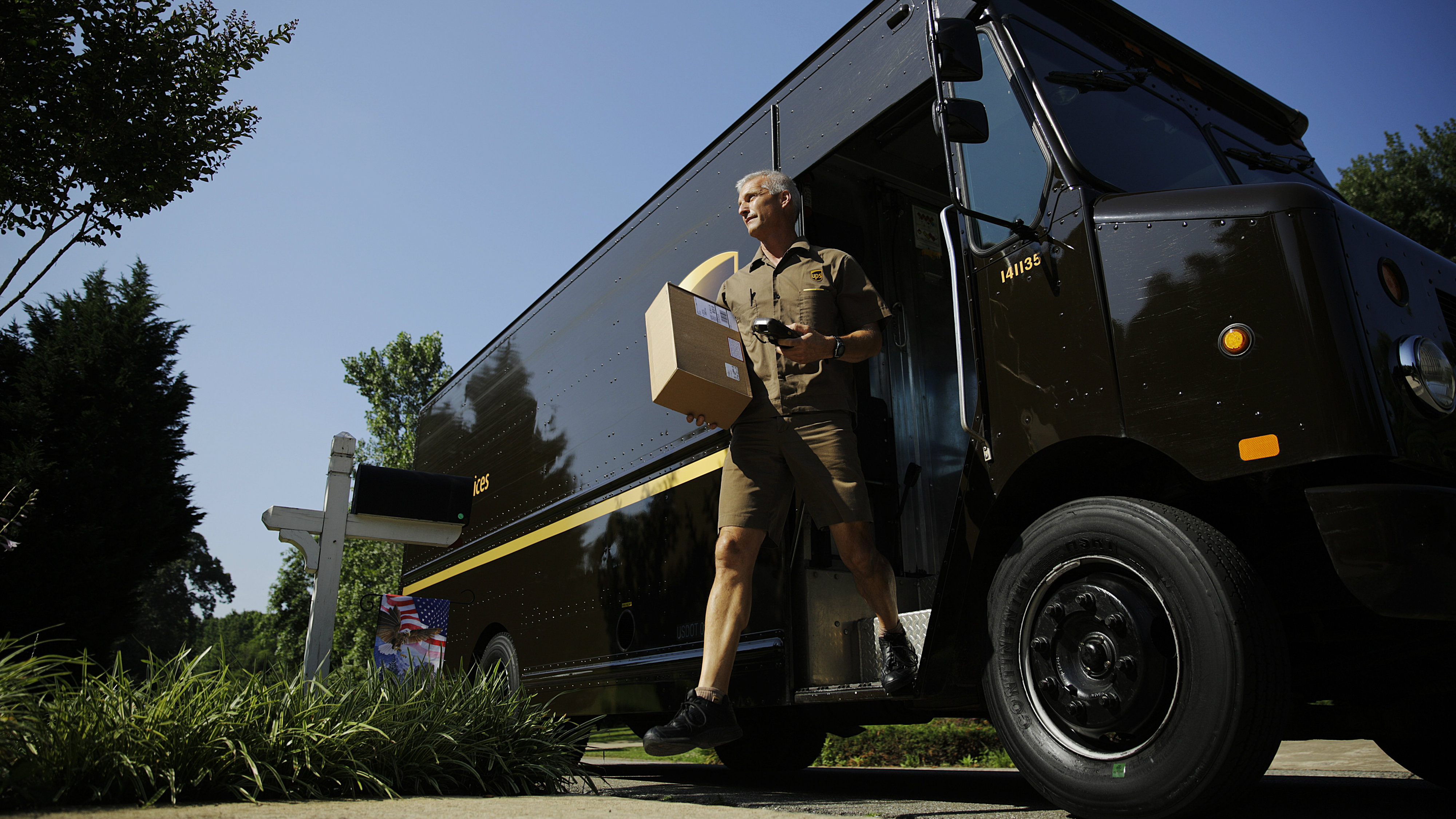 In this June 20, 2014 photo, United Parcel Service driver Marty Thompson steps off a truck while making a delivery in Cumming, Ga. (AP Photo/David Goldman)