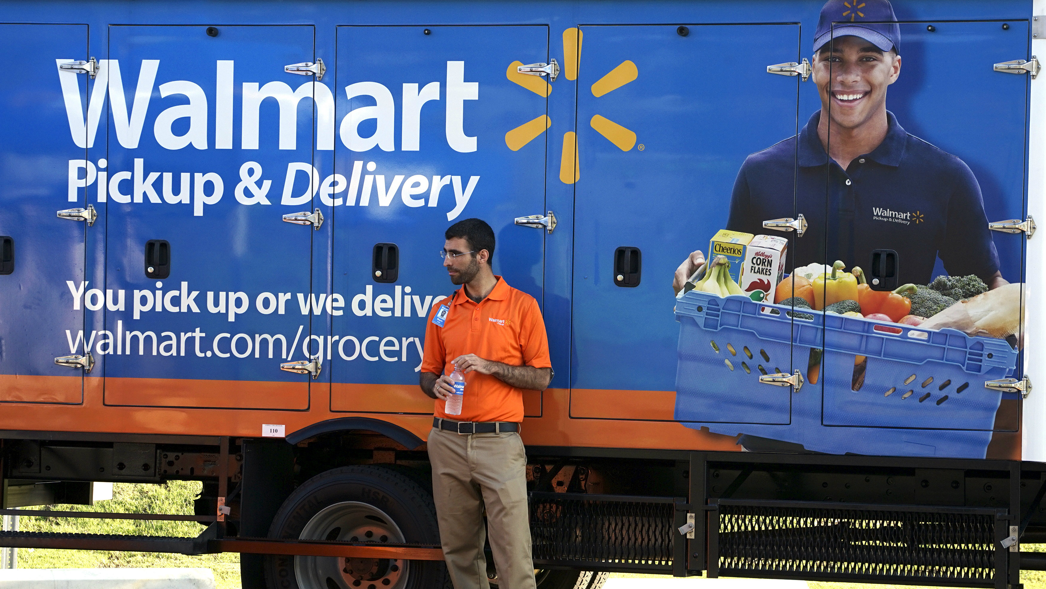 A man standing in front of a Wal-Mart delivery truck