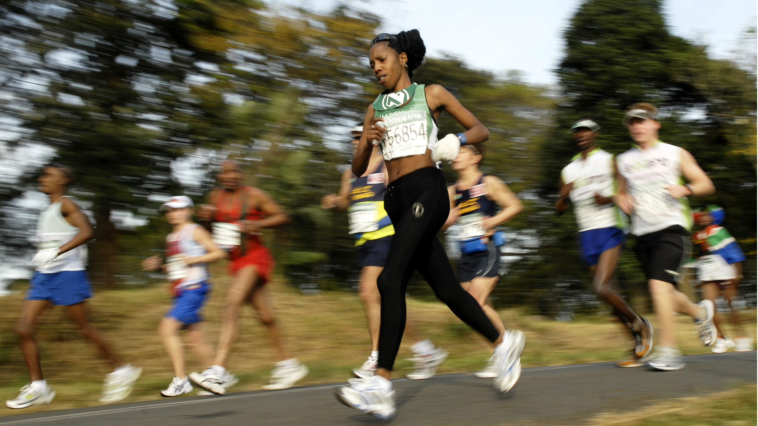 Runners in an ultra marathon; one woman is in focus, the rest blurred behind her.