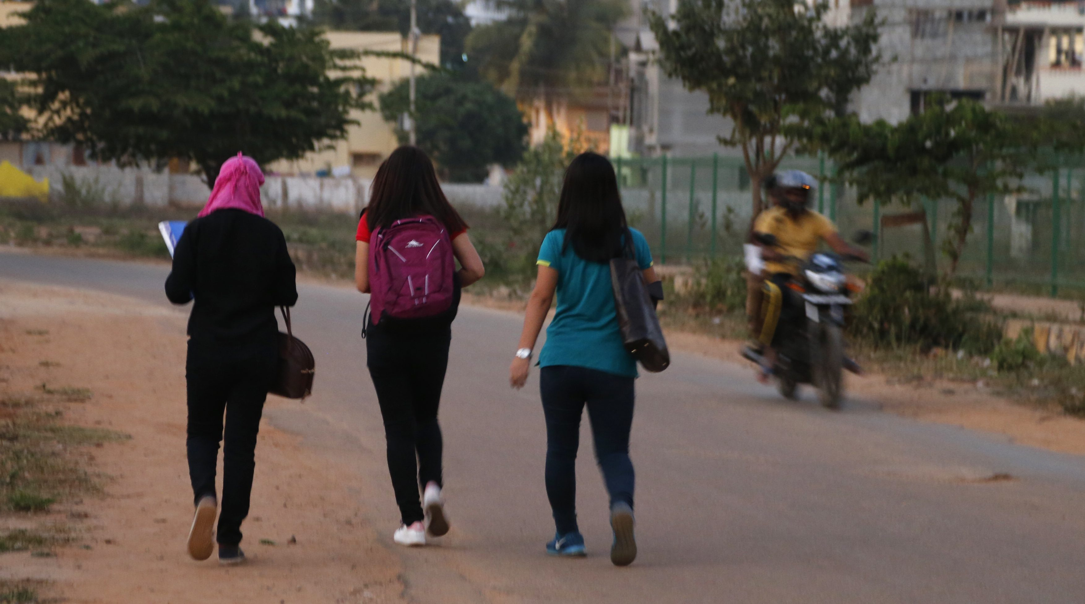 A motorist rides past young Indian girls in Bangalore, India, Wednesday, Jan. 4, 2017. Police detained at least six suspects Wednesday, days after outrage erupted in India over several women being groped and molested during New Year's Eve celebrations in the southern city of Bangalore, the country's information technology hub. The incident highlights the persistent violence against women in India despite tougher laws against sexual assault imposed after the December 2012 death of a young woman who was gang-raped on a bus in New Delhi.