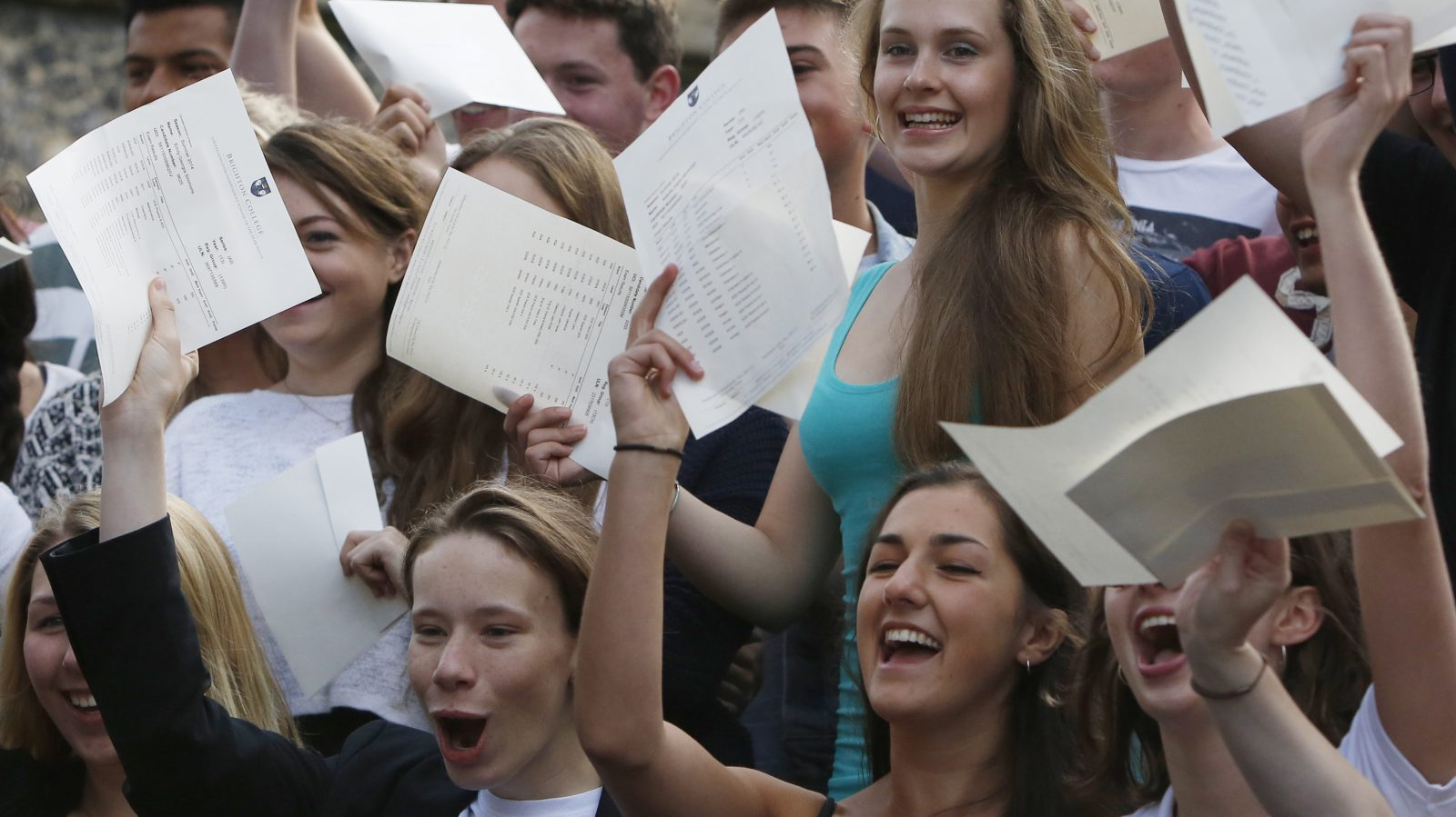 A-level student Tabitha Jackson (top R) poses with classmates for photographs, after she received her results of 4 A* A-levels, with a passrate of 99% dropping only 14 points out of a possible 1600, at Brighton College in Brighton, southern England August 14, 2014.  Hundreds of thousands of teenage students received A-level results in England, Wales and Northern Ireland on Thursday. REUTERS/Luke MacGregor  (BRITAIN - Tags: EDUCATION SOCIETY) - RTR42EL4