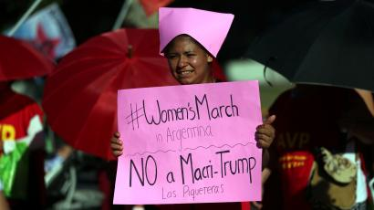 """A woman wear a pink protest hat, symbol of the anti-Trump women's march, during a protest outside the U.S. embassy in Buenos Aires, Argentina, January 20, 2017. The signs read """"No to Trump - Leftist socialist (party)"""" REUTERS/Marcos Brindicci - RTSWLIU"""