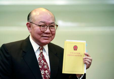 Retired judge Woo Kwok-hing holds a copy of the Basic Law, the territory's mini constitution, as he announces his run in next year's chief executive election during a news conference in Hong Kong, Thursday, Oct. 27, 2016. (AP Photo/Kin Cheung)