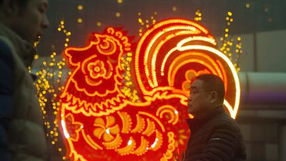 Chinese men walk past neon decorations marking the Year of the Rooster in Beijing, China, Monday, Jan. 16, 2017. The Lunar New Year which falls on Jan. 28 this year marks the Year of the Rooster in the Chinese calendar. (AP Photo/Ng Han Guan)