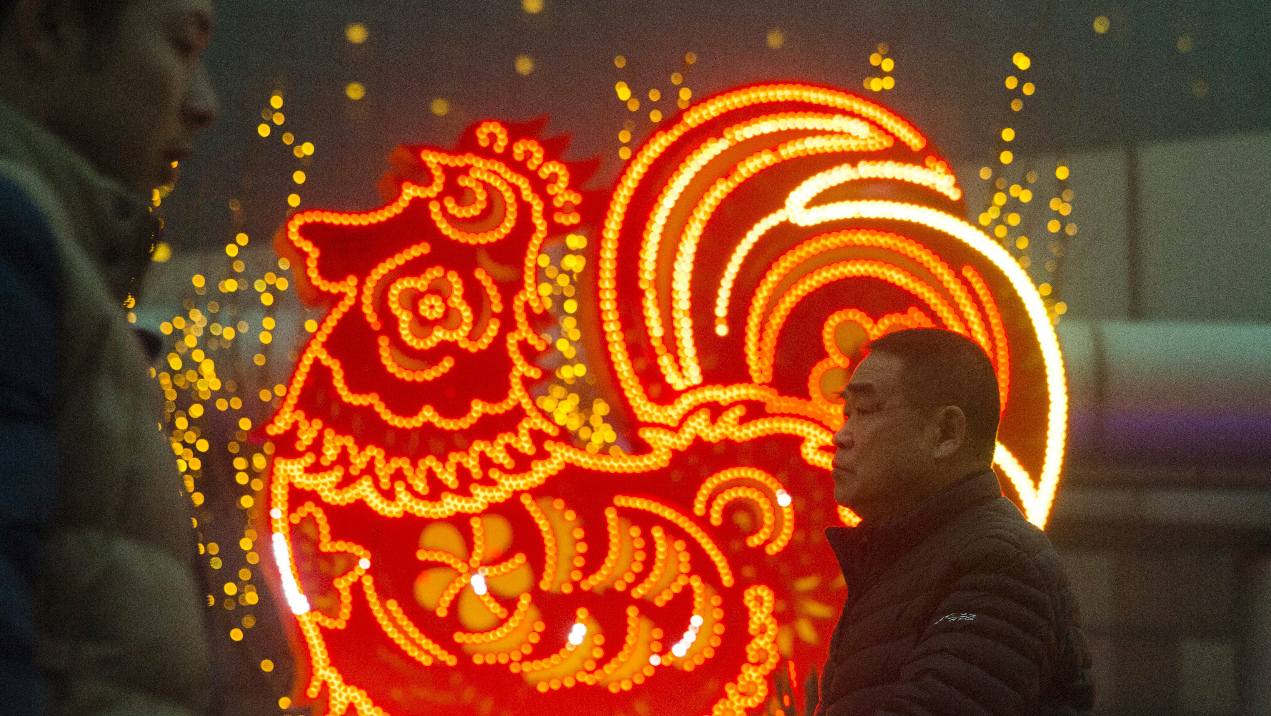 Chinese new year 2018 how to prepare for lunar new year chinese men walk past neon decorations marking the year of the rooster in beijing china kristyandbryce Image collections