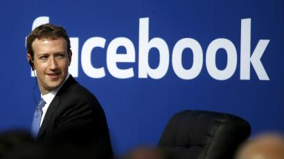 Zuckerberg in front of facebook logo