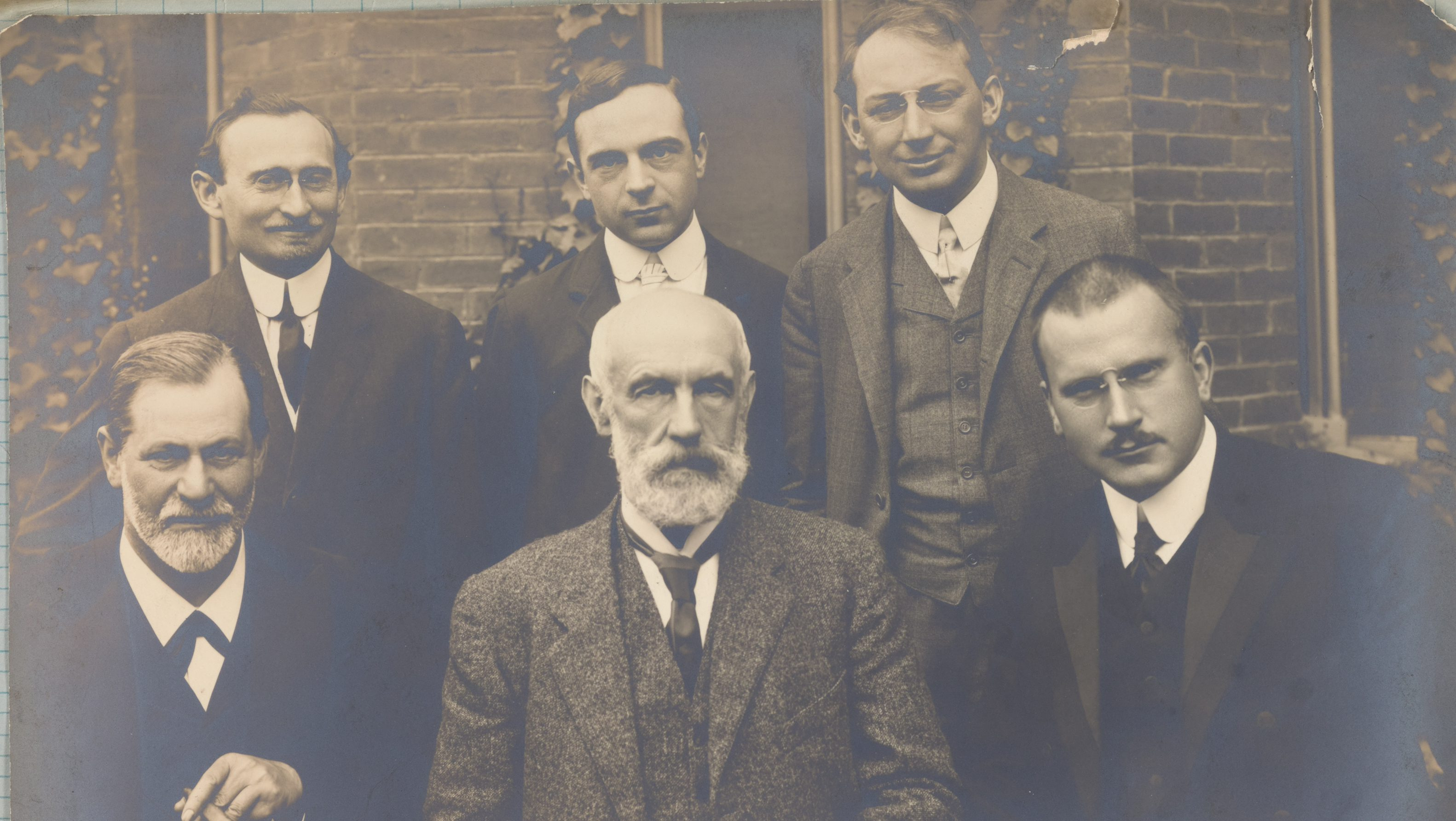 "Shown in this photograph from left to right in the front row are Freud, Clark University president G. Stanley Hall, and Carl Jung, with Abraham A. Brill, Ernest Jones, and Sándor Ferenczi standing behind them. Freud later wrote in an autobiographical work that the positive reception of his theories received in America convinced him that ""psychoanalysis was not a delusion any longer; it had become a valuable part of reality."""
