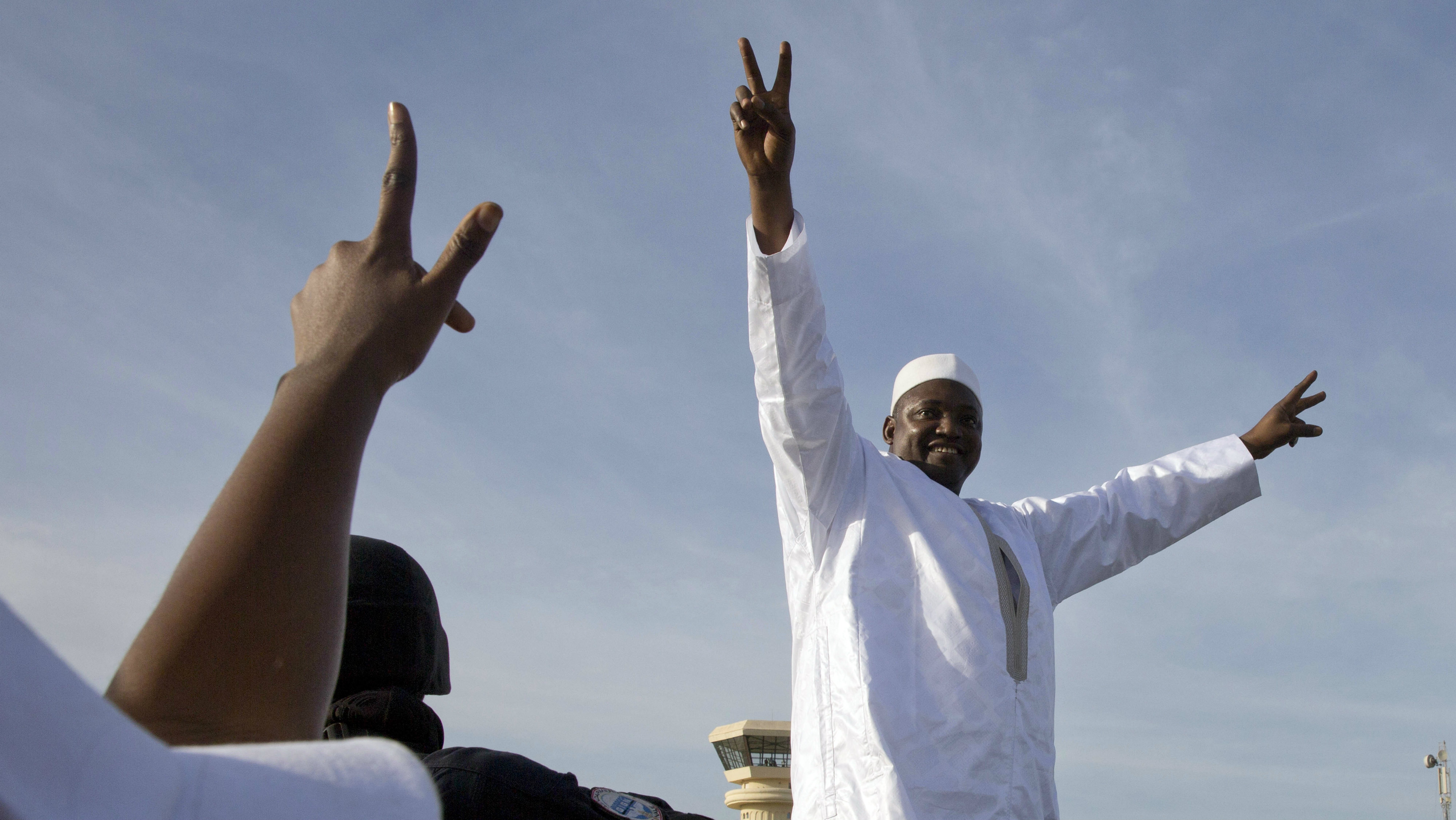 Gambian President Adama Barrow greets the crowds after arriving at Banjul airport in Gambia, Thursday Jan. 26, 2017, after flying in from Dakar, Senegal. Gambia's new president has finally arrived in the country, a week after taking the oath of office abroad amid a whirlwind political crisis. Here's a look at the tumble of events that led to Adama Barrow's return — and the exile of the country's longtime leader.
