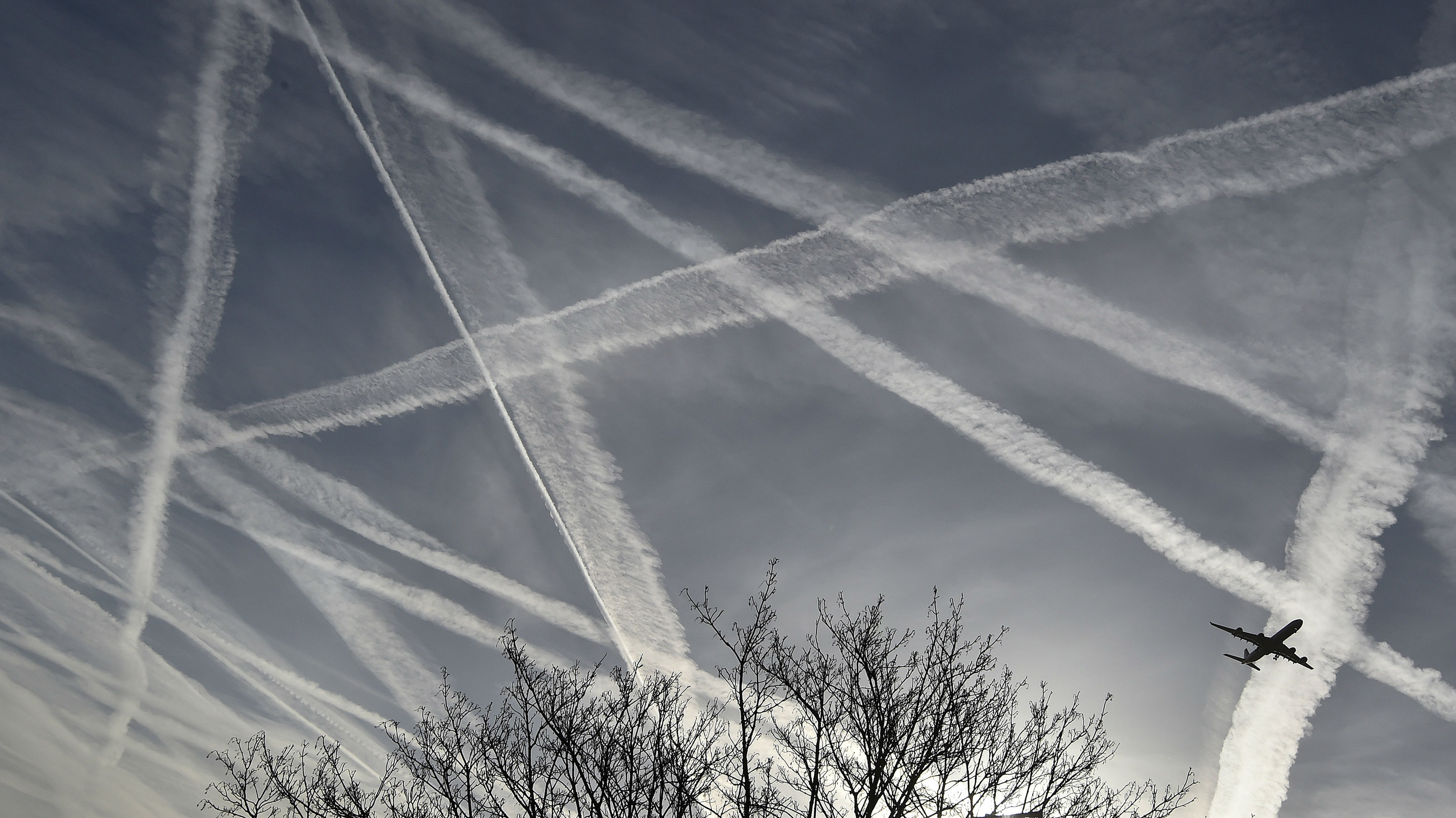 A passenger plane flies through aircraft contrails in the skies near Heathrow Airport in west London, April 12, 2015.