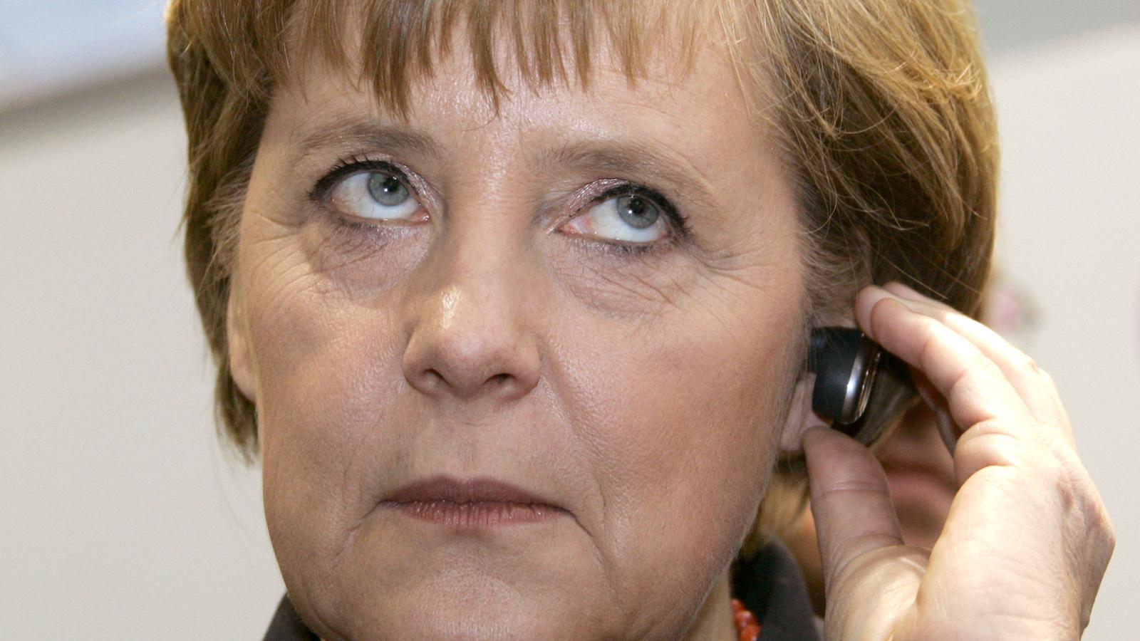 German Chancellor Angela Merkel uses a Motorola Bluetooth mobile phone headset