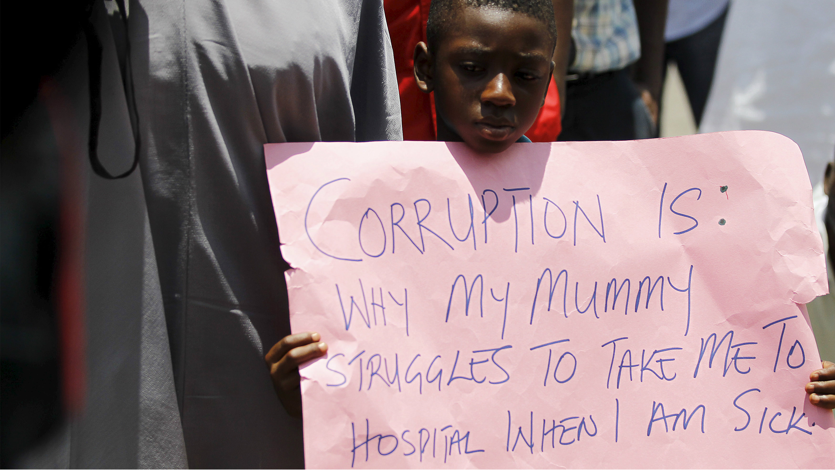 A boy holds a placard during a rally in support of President Muhammadu Buhari's anti-corruption campaign, at the gate of the presidential villa in Abuja, Nigeria August 17, 2015.