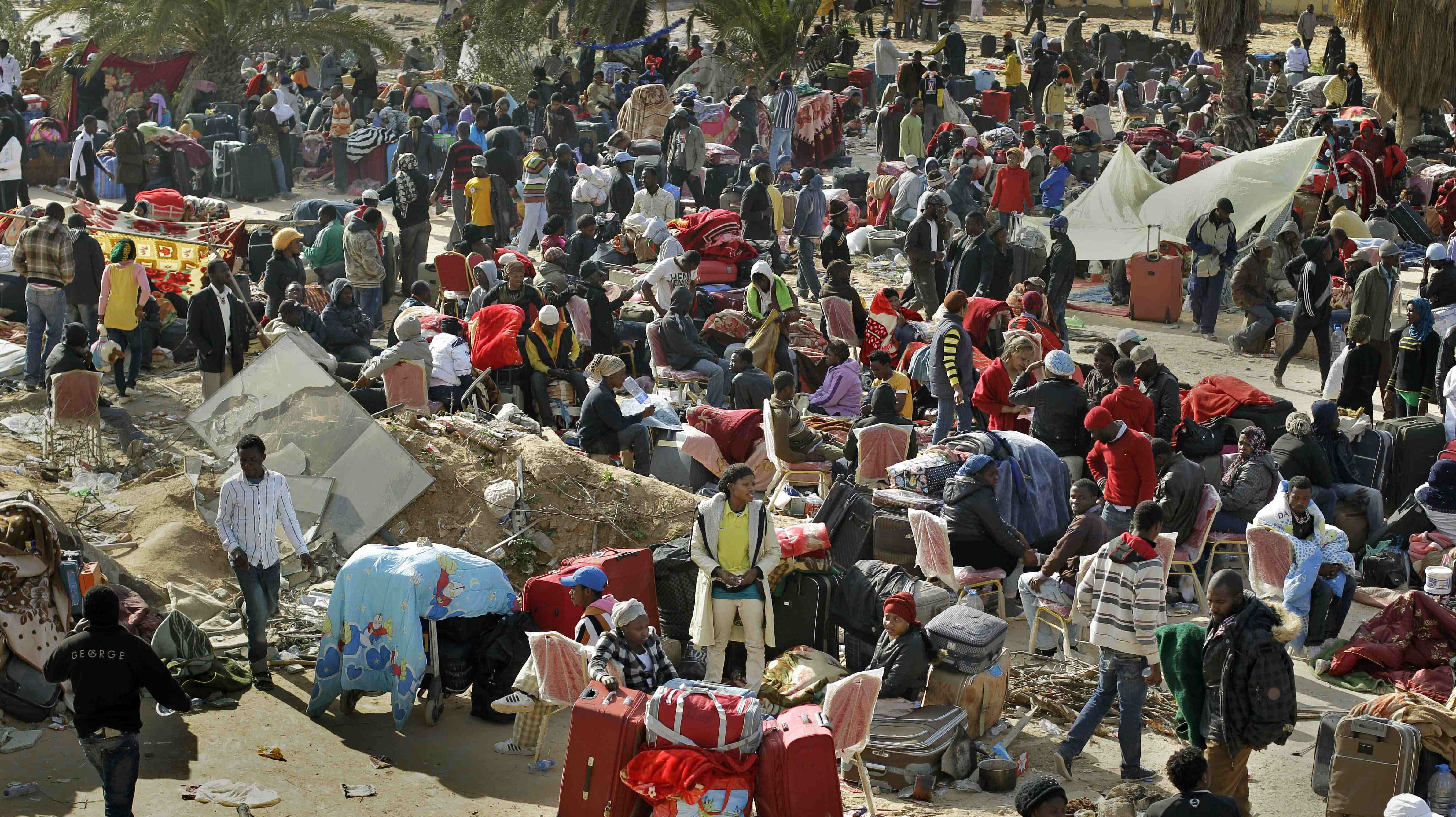 Nigerians and Ghanaians sit with their belongings in a makeshift open-air camp at Tripoli International Airport in Libya Tuesday, March 1, 2011. While many European countries evacuated their citizens from Libya, thousands of foreigners including migrant workers from Egypt and Sub-Saharan countries such as Nigeria and Ghana have been camped out at the airport for over a week, many unable to leave the country and fearing for their safety in the unstable situation. (AP Photo/Ben Curtis)