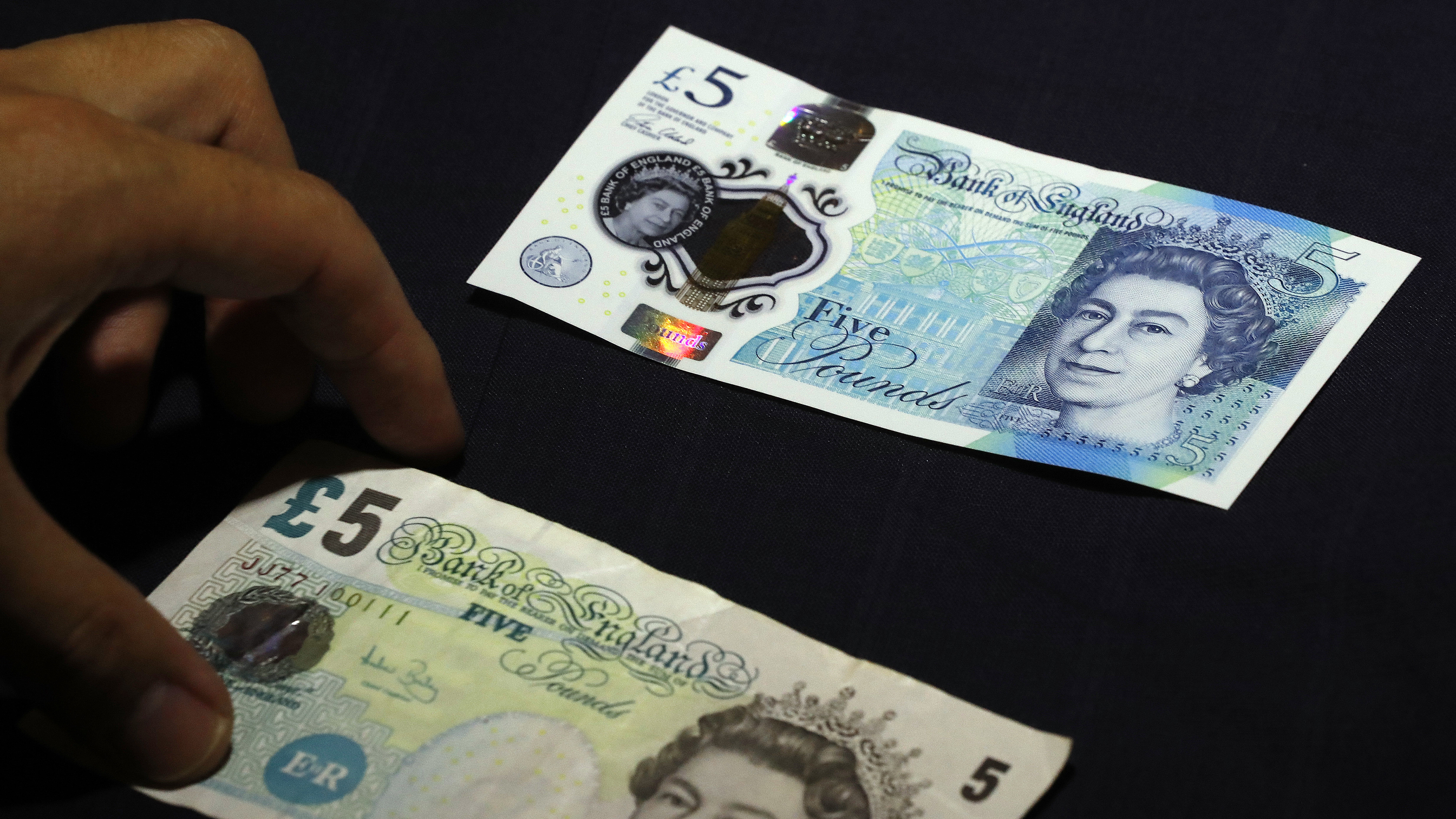 A new five pound note on top of an old one is shown at the Bank of England Museum in London, Tuesday, Sept. 6, 2016. A new gallery opening at the Bank of England Museum marks the launch of the new polymer fiver, which will go into circulation next Tuesday (AP Photo/Frank Augstein)
