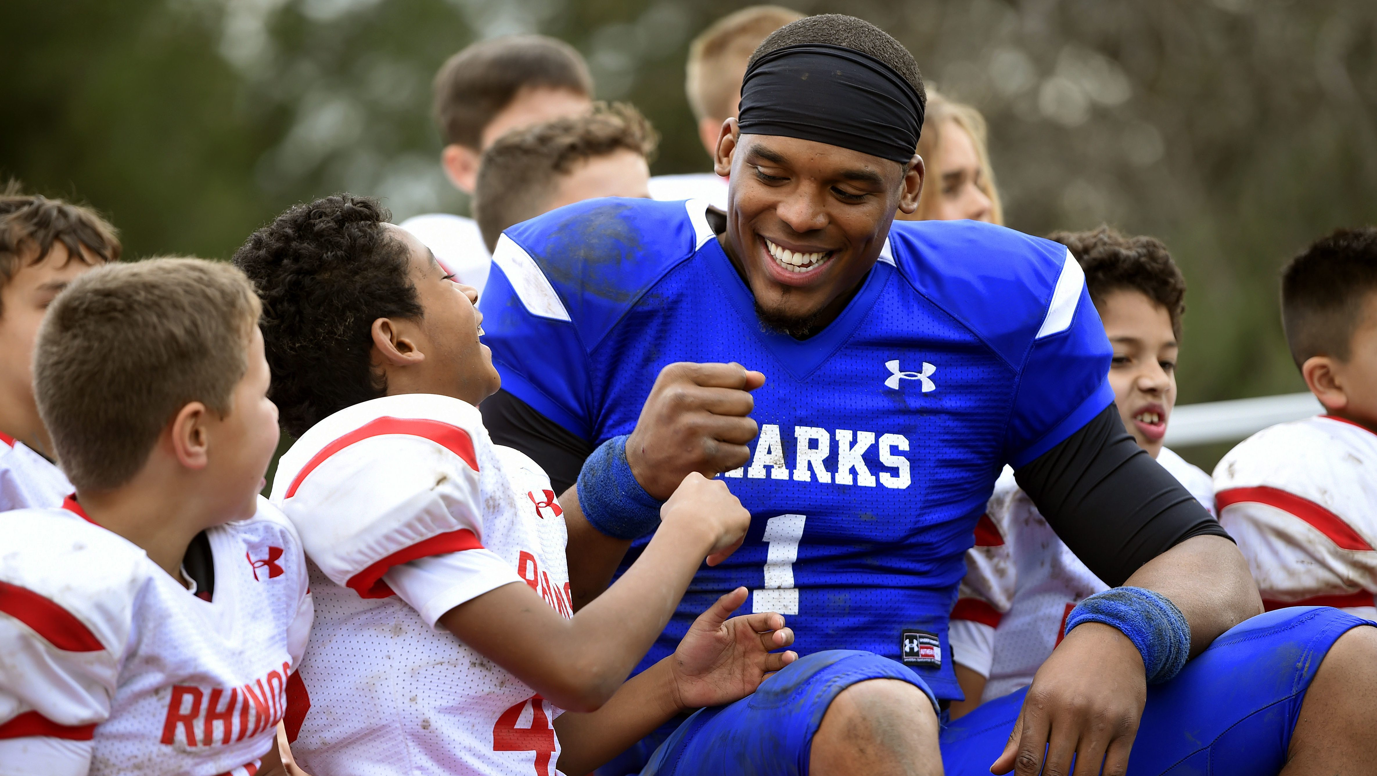 This Jan. 13, 2017 photo shows NFL player Cam Newton, right, bumping fists with youth football player Keilan Matthews, 8, of Santa Clarita, Calif., during the filming of a Buick commercial for this year's Super Bowl telecast in Los Angeles.  The commercial is set to air during the first quarter.  (Photo by Chris Pizzello/Invision/AP)
