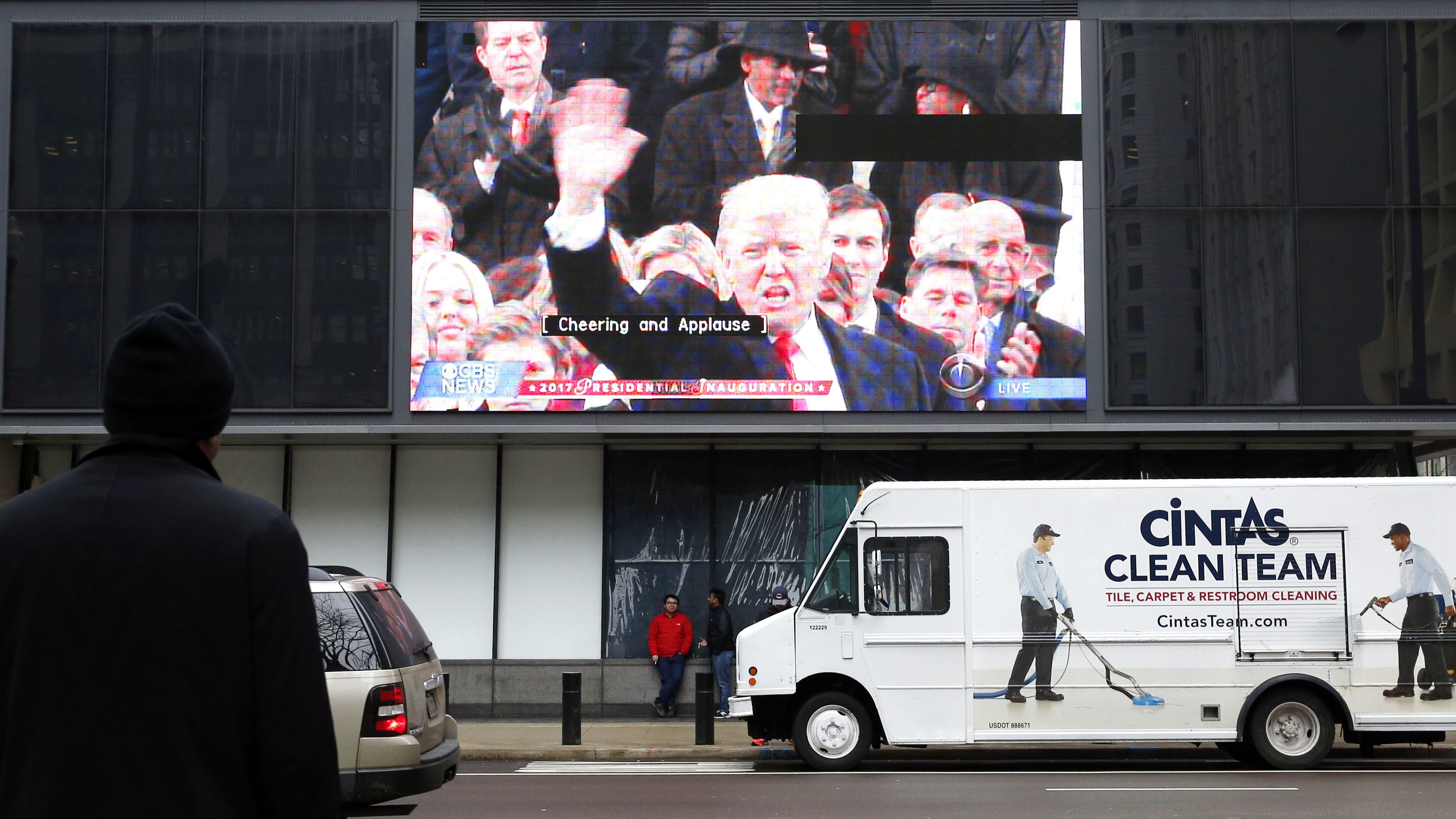 People walk by a big screen tv as it displays the presidential inauguration of Donald Trump in downtown Chicago Friday, Jan. 20, 2017. (AP Photo/Nam Y. Huh)